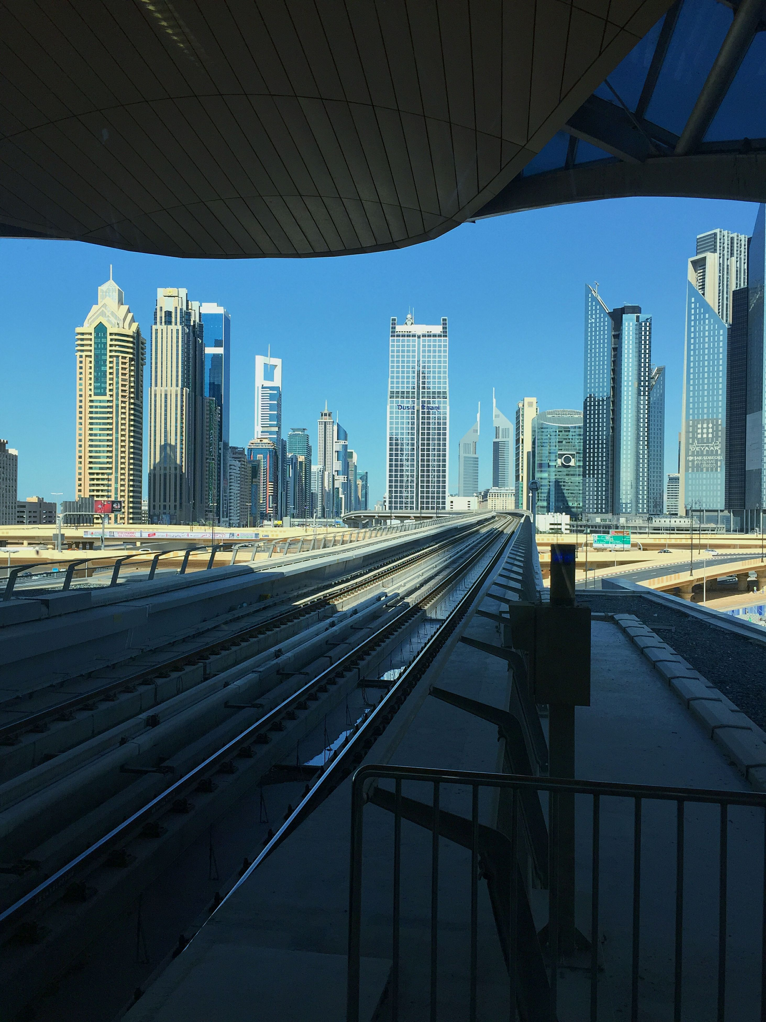 architecture, built structure, building exterior, transportation, railroad track, city, clear sky, the way forward, diminishing perspective, rail transportation, public transportation, blue, railroad station platform, modern, skyscraper, vanishing point, sky, railroad station, office building, day