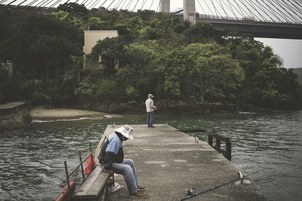 Men Fishing In Sea From Walkway