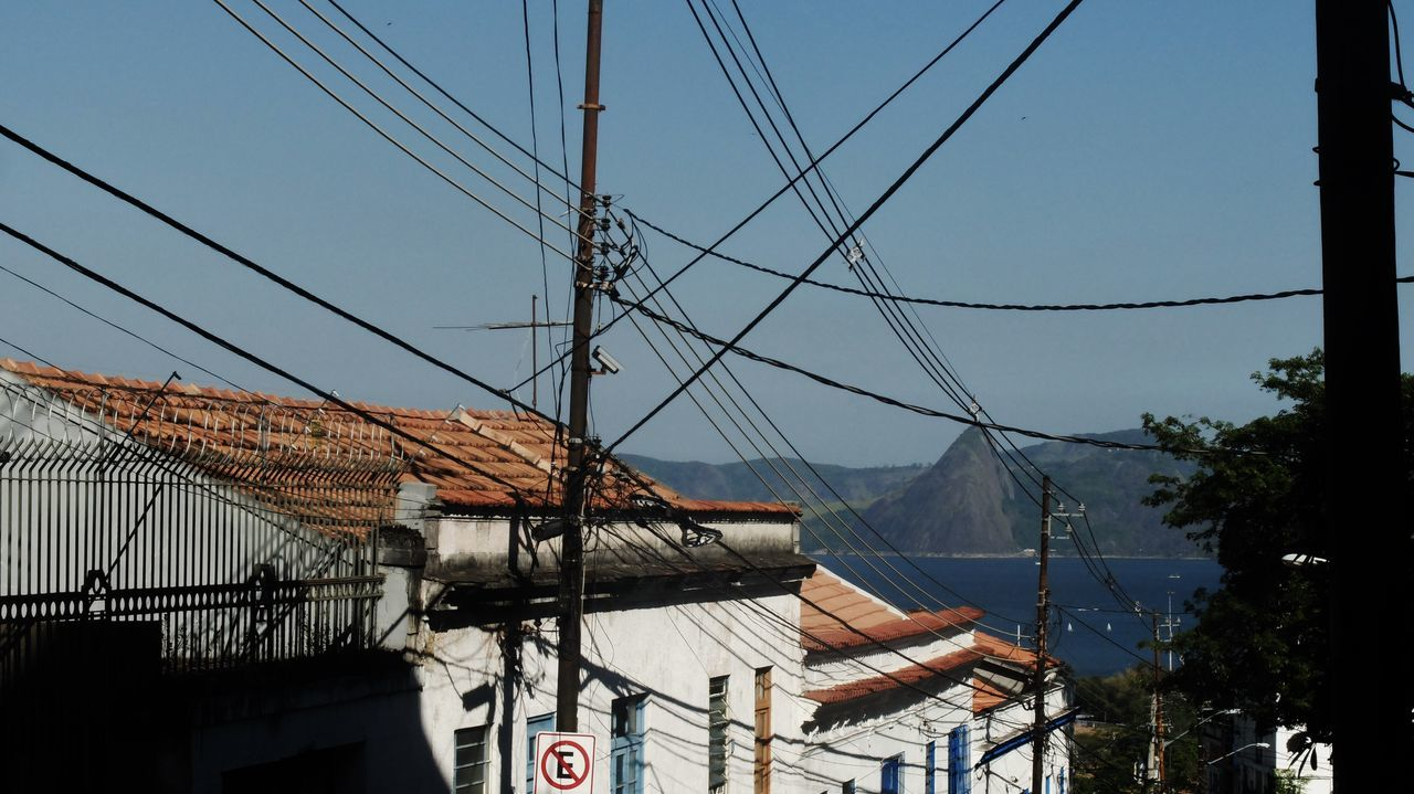 Power Lines By Houses Against Sky