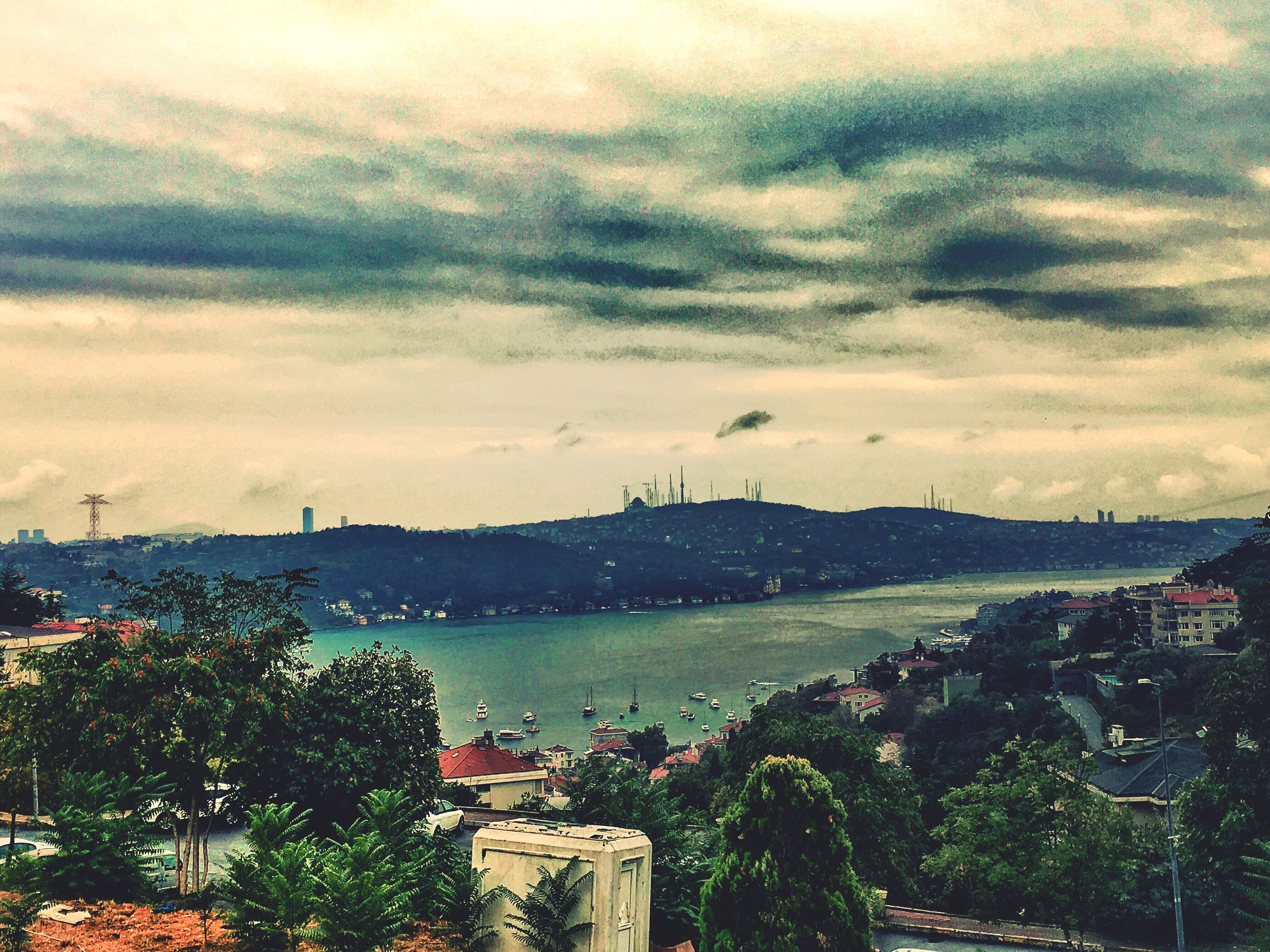 cloud - sky, city, water, tree, cityscape, sky, high angle view, cloudy, architecture, cloud, travel destinations, mountain, sea, scenics, growth, tourism, day, residential district, city life, tranquil scene, outdoors, mountain range, storm cloud, suspension bridge, cloudscape, development, beauty in nature, tranquility