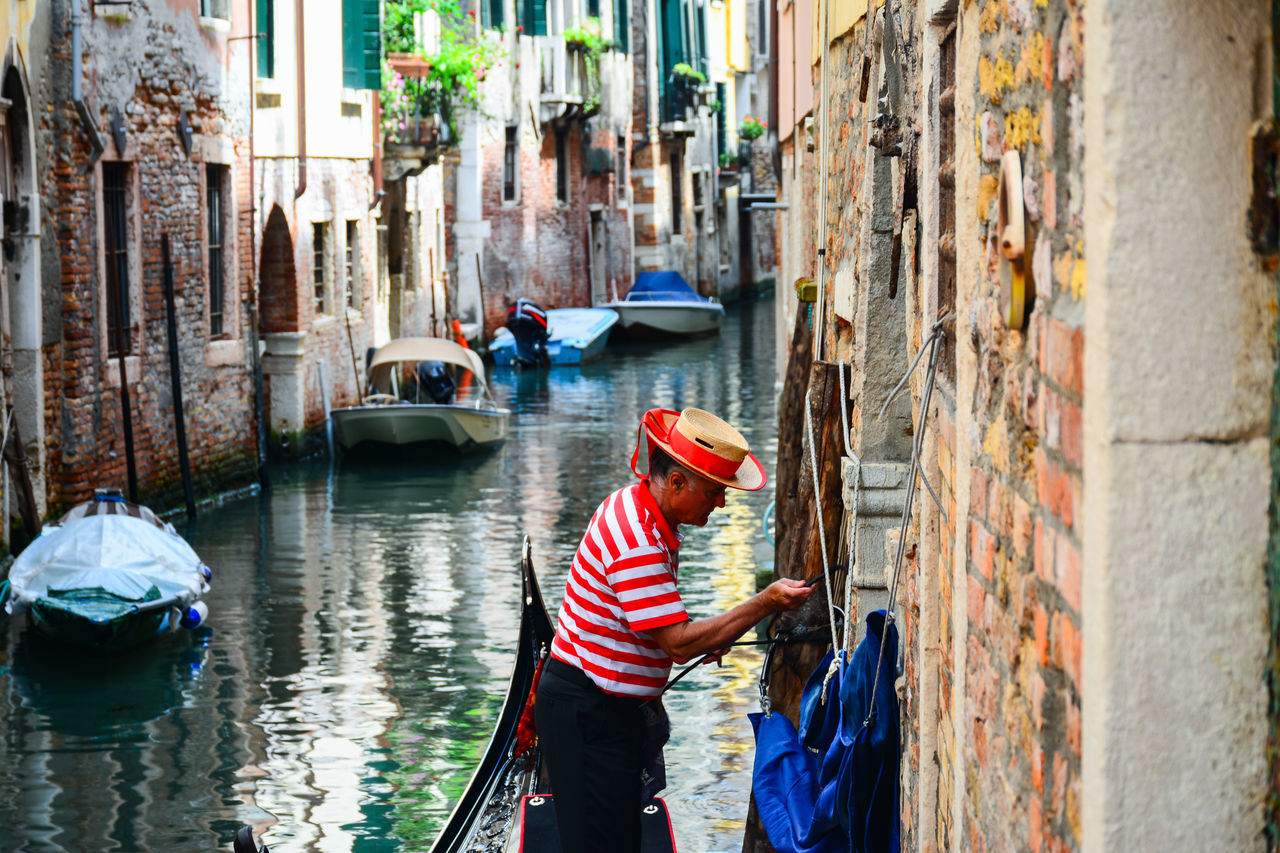 real people, canal, architecture, built structure, men, building exterior, gondolier, day, gondola - traditional boat, leisure activity, outdoors, water, nautical vessel, lifestyles, standing, women, one person, people