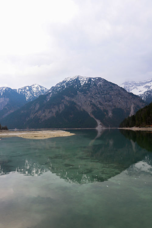 Reflections on a lake Alps Alps Austria Austria Beauty In Nature Cloud - Sky Clouds Day Lake Landscape Mountain Mountain Range Nature No People Outdoors Plansee Reflection Scenery Scenics Sky Snow Tranquil Scene Tranquility Water Waterfront Betterlandscapes