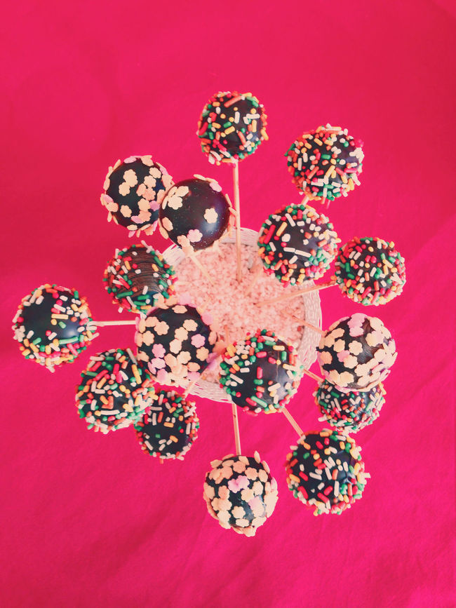 Colorful chocolate cakepops on red background top view Cake Cakepop Cakepops Candy Chocolate Close-up Dessert Directly Above Freshness Gourmet High Angle View Indoors  Party Popcake Red Sprinkles Stick Sugar Sweet