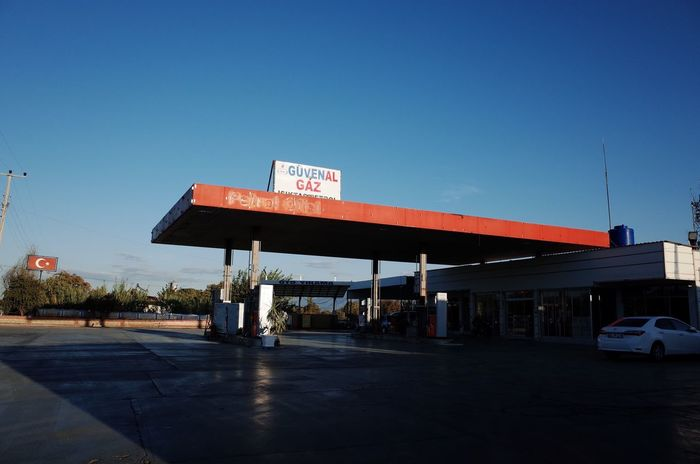 Transportation Gas Station Car Text Land Vehicle Refueling Mode Of Transport Blue Fuel Pump Day Clear Sky Road Gasoline Outdoors Built Structure Architecture Road Sign No People Sky Parking Garage