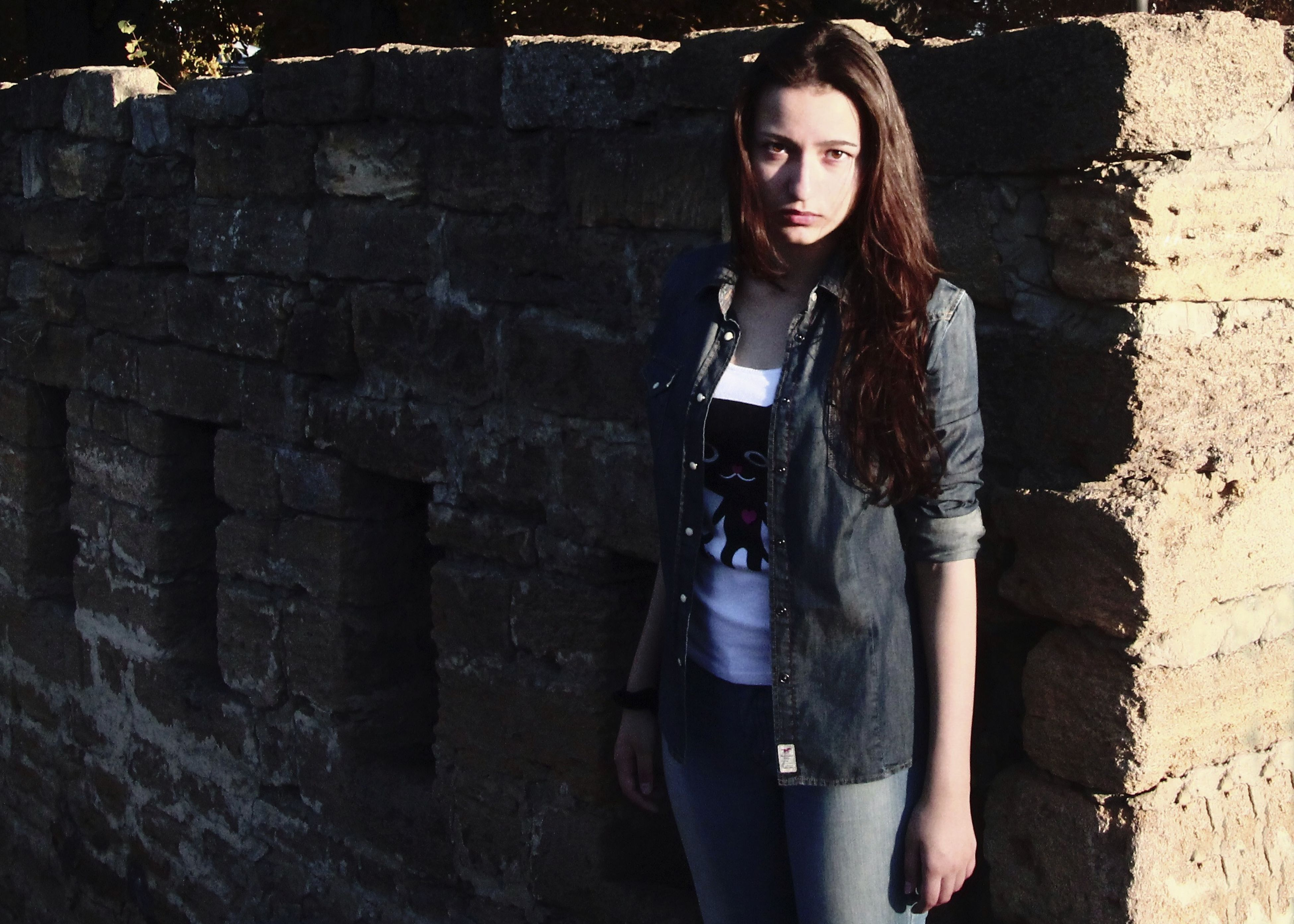 young adult, young women, person, portrait, looking at camera, lifestyles, front view, casual clothing, standing, leisure activity, smiling, fashion, architecture, built structure, long hair, wall - building feature, three quarter length