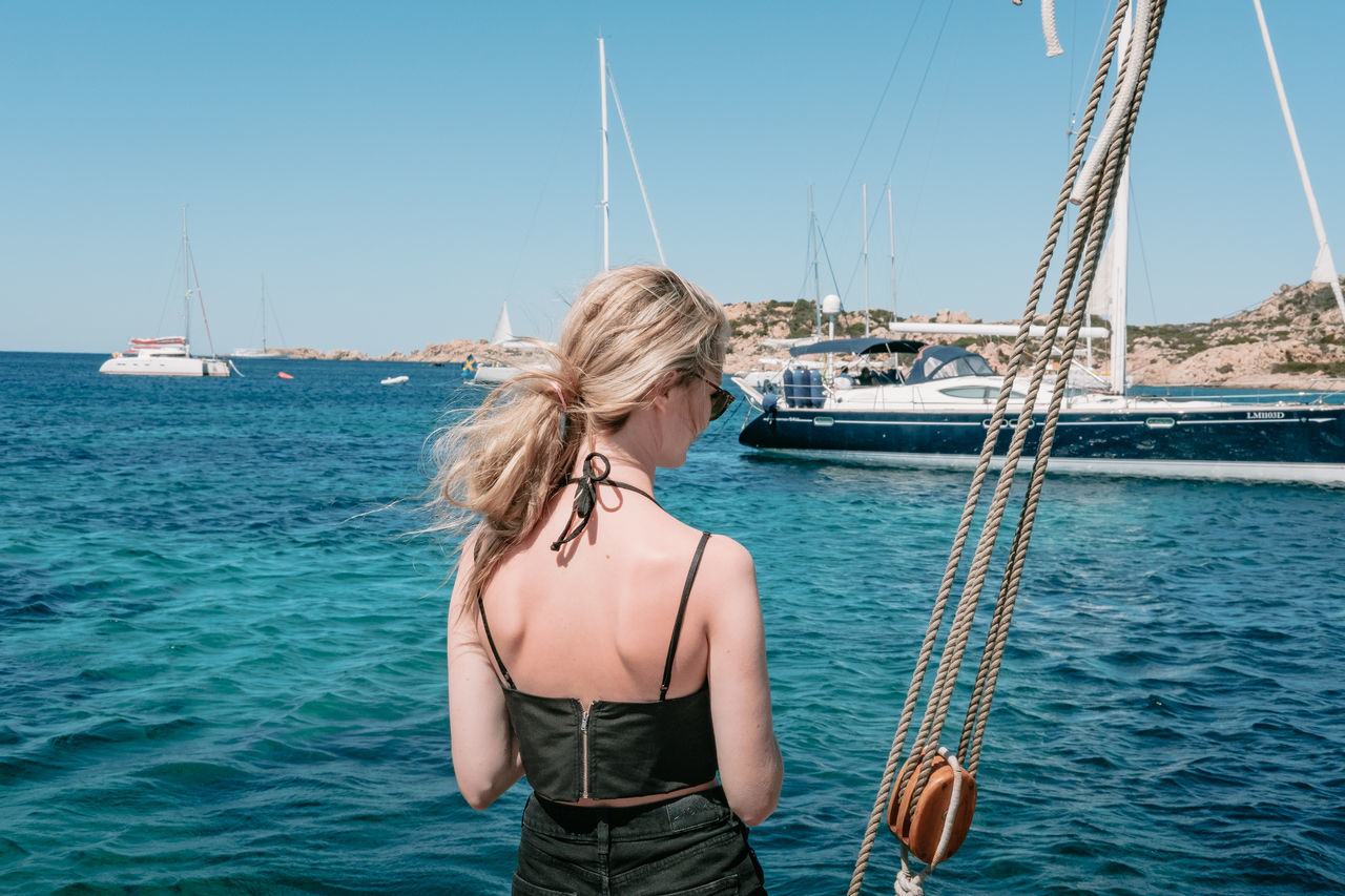 real people, sea, nautical vessel, one person, mode of transport, rear view, water, transportation, casual clothing, standing, young adult, young women, day, lifestyles, blond hair, outdoors, clear sky, nature, sky, people