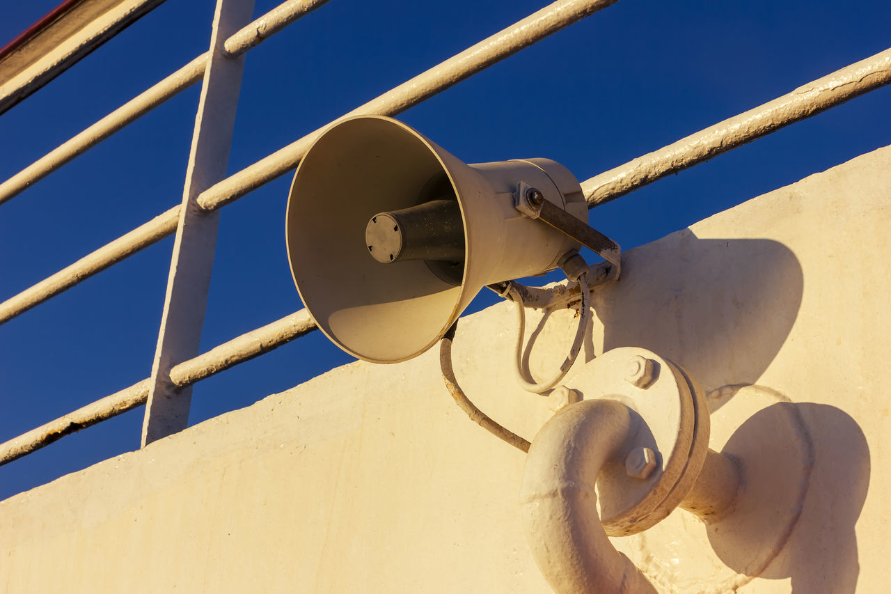 white megaphone on deck of a ferry Blue Boat Clear Sky Close-up Communication Deck Equipment Ferry Installation Loudspeaker Megaphone Message Railing Shadow Sunlight Technology Transportation