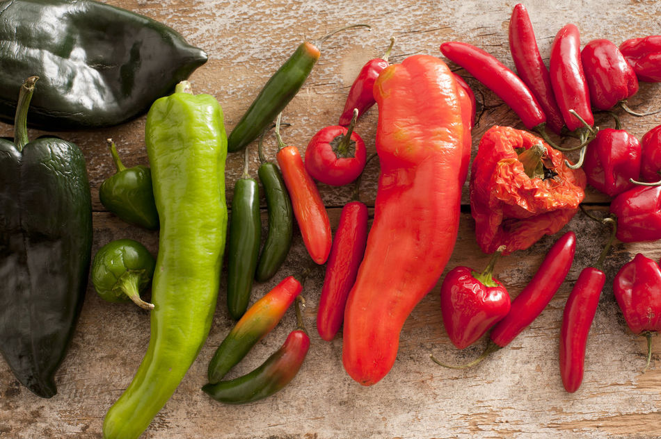Different varieties and colors of whole fresh chili peppers arranged in a line on a wooden table with red, green and black peppers viewed from above Cayenne Chili  Culinary Food And Drink Fresh Green High Angle View Indoors  Ingredients Mexican Natural Organic Overhead Pepper Raw Red Red Red Chili Pepper Sizedoesntmatter Spicy Table Various Vegetable Vegetables