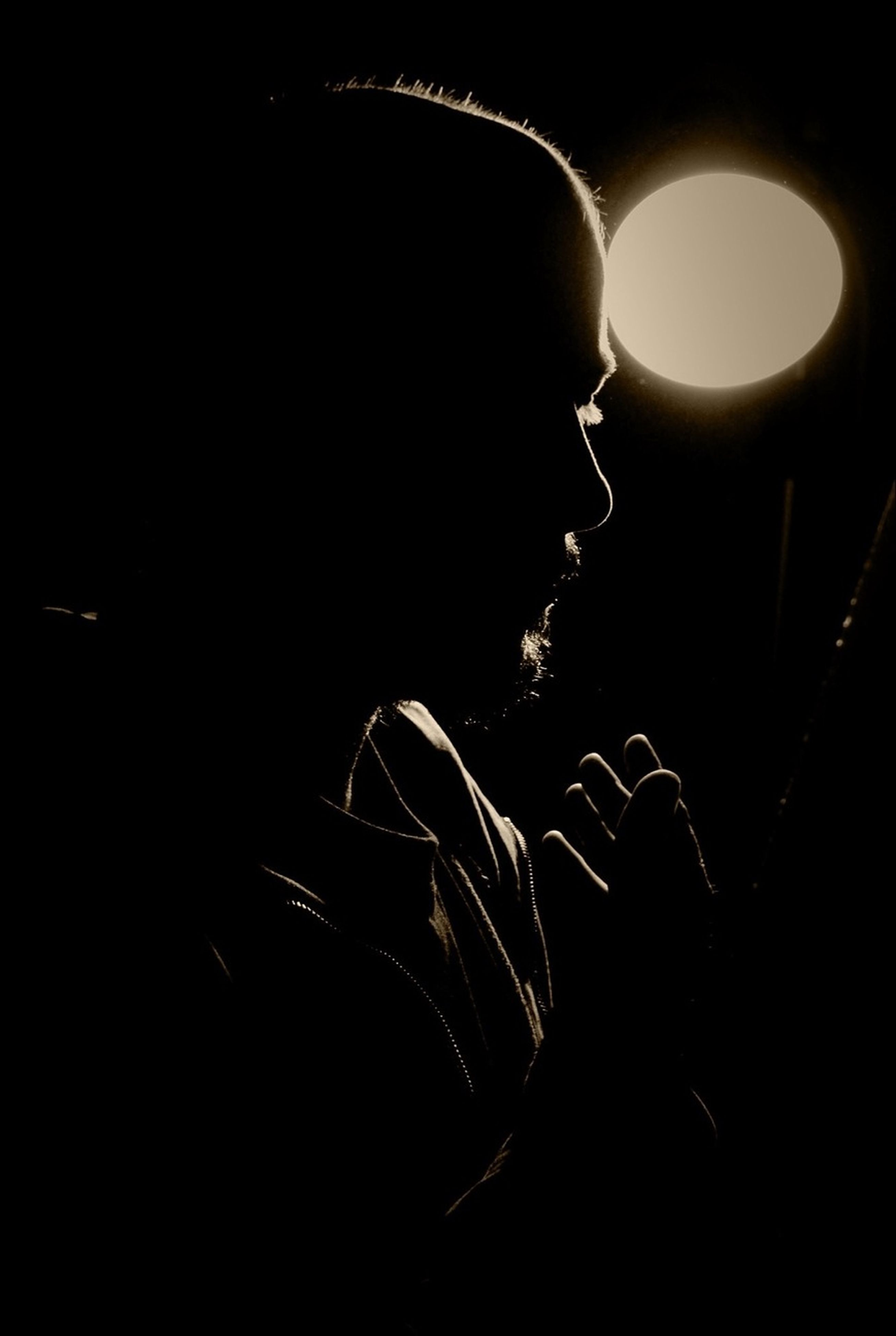lifestyles, leisure activity, night, men, indoors, illuminated, arts culture and entertainment, dark, music, silhouette, person, light - natural phenomenon, young adult, standing, unrecognizable person, studio shot, holding, performance
