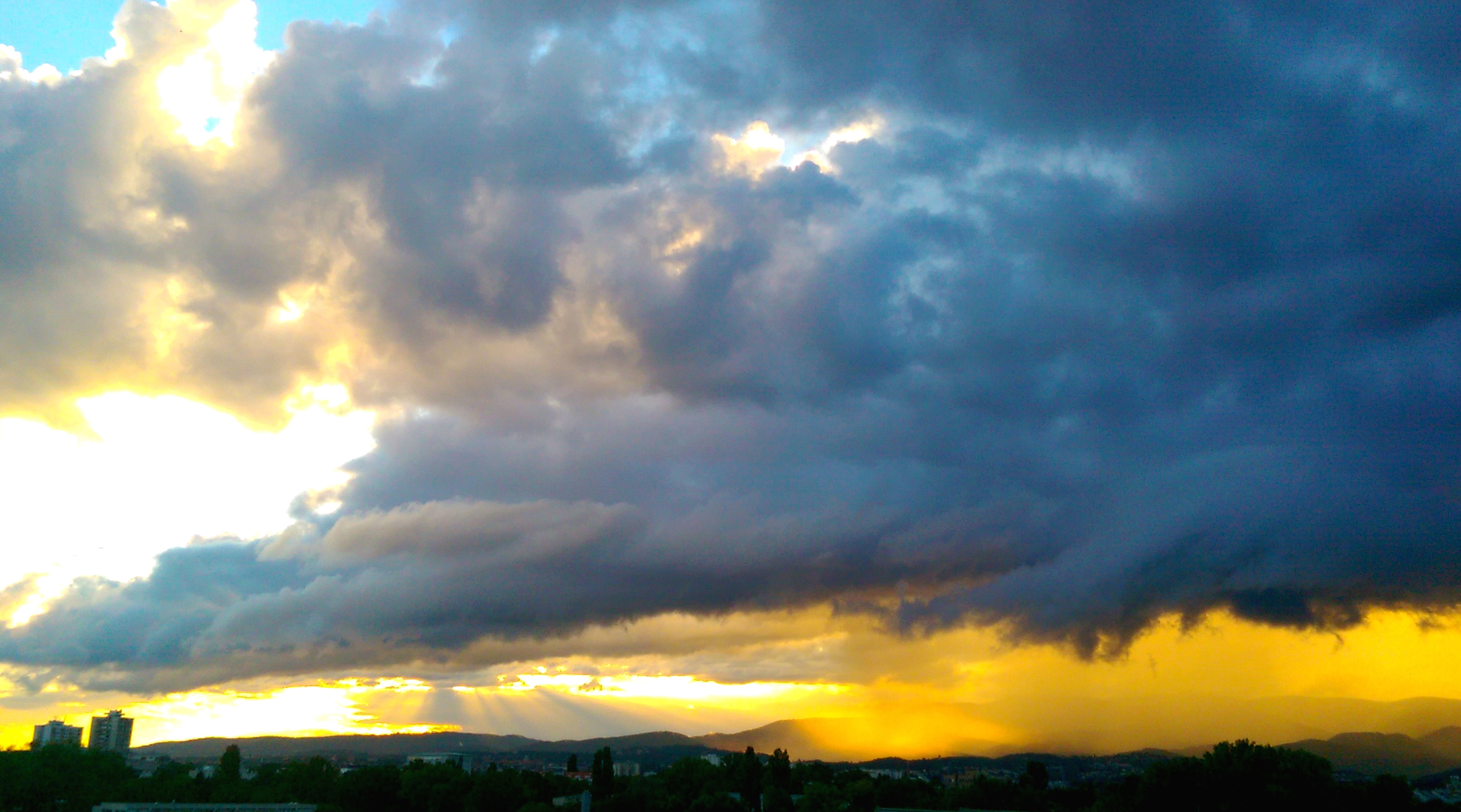 sunset, sky, cloud - sky, dramatic sky, orange color, scenics, beauty in nature, cloudy, silhouette, cloud, weather, tranquil scene, building exterior, nature, moody sky, tranquility, atmospheric mood, cloudscape, idyllic, overcast