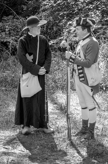 Aug 4 2017 Niles Michigan USA; two men in costumes , have a conversation during the fort st Joesph historical project open house Soldier Religion Weopons Friendship Recreation  Uniform Adult Costumes Day Field Friar Full Length Grass Guns Hats History Holding Men Miltary Nature Outdoors People Reenactors Religion Standing Two People