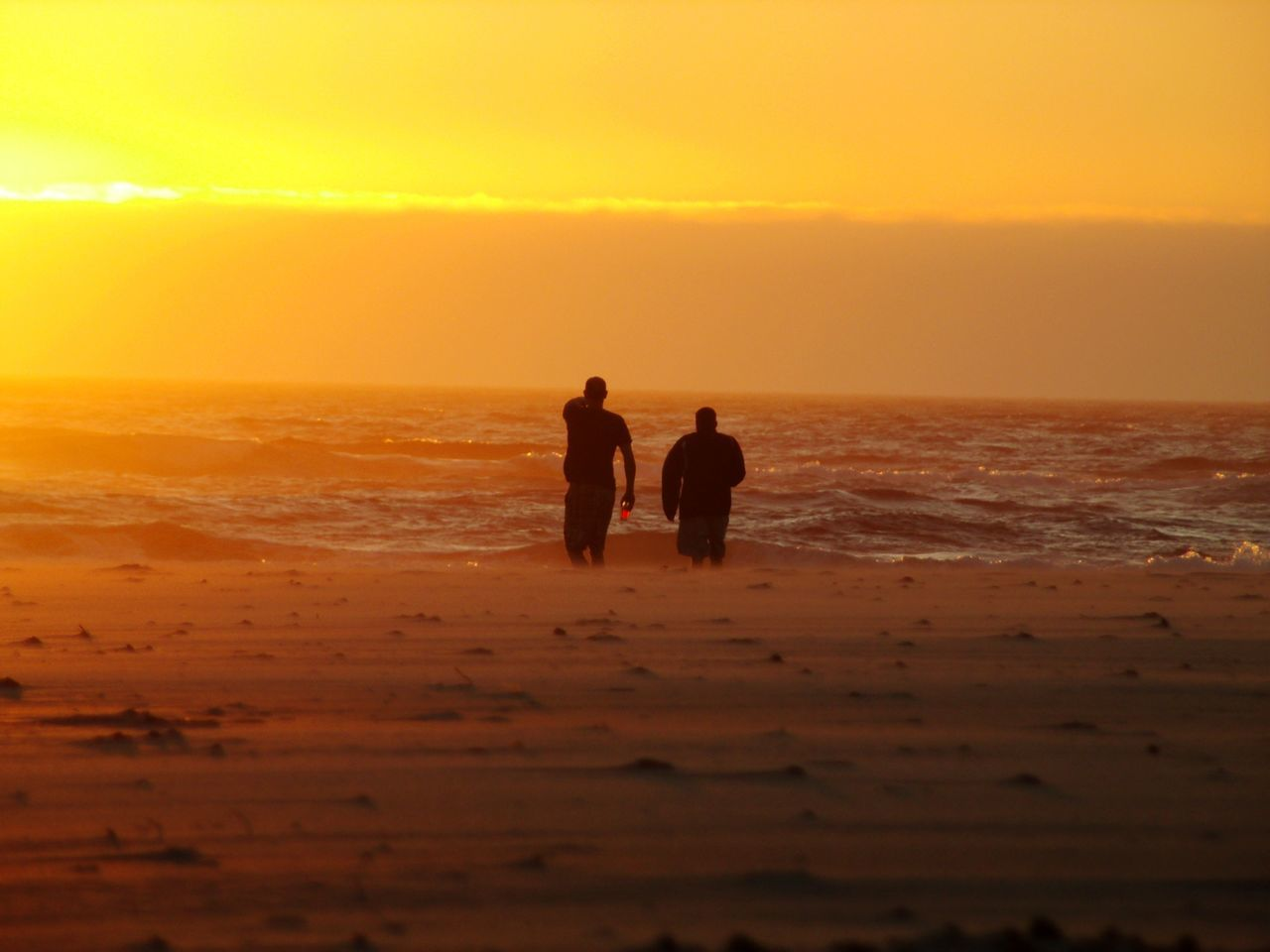 sunset, sea, silhouette, beach, nature, water, beauty in nature, scenics, togetherness, real people, leisure activity, horizon over water, men, sand, sky, standing, lifestyles, friendship, vacations, two people, outdoors, wave, day, people
