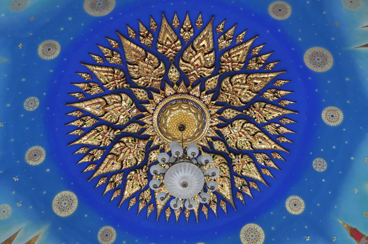 The ceiling in the Buddhist temple is decorated with chandelier and Thai pattern. Art And Craft Blue Blue Sky Buddhist Temple In Thailand Cataract Ceiling Chandelier Circle Close-up Day Gold Colored Heaven Indoors  Murals No People Painting Pattern Sky Star Thai Pattern