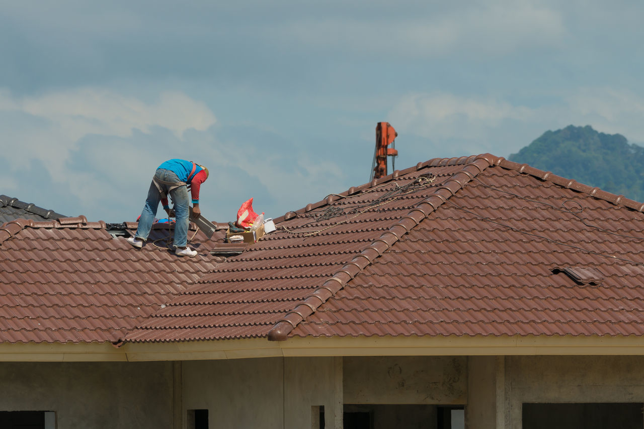 roof, architecture, built structure, building exterior, house, day, roof tile, outdoors, sky, tiled roof, real people, manual worker, people