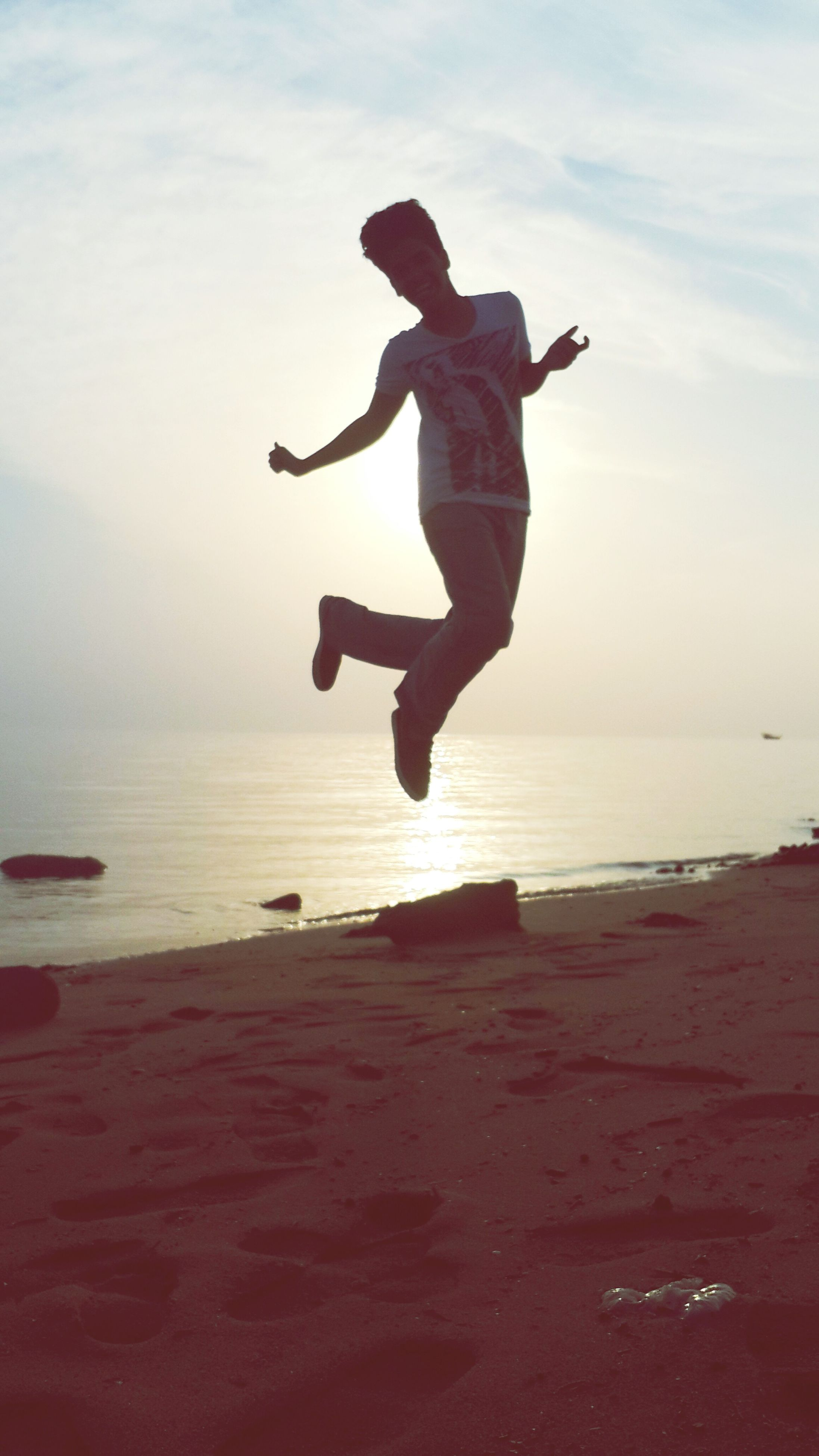 full length, sea, beach, leisure activity, mid-air, jumping, lifestyles, sky, enjoyment, shore, fun, water, sand, vacations, freedom, arms raised, arms outstretched, horizon over water