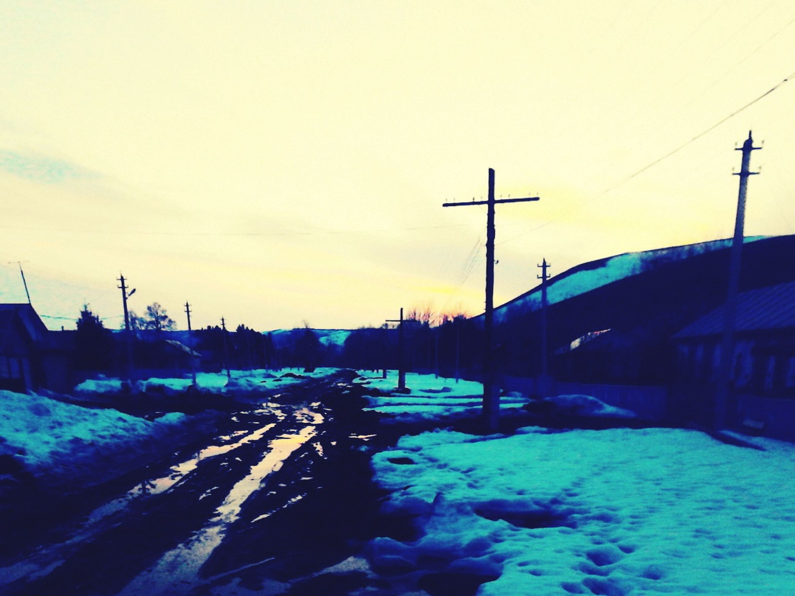 snow, winter, cold temperature, season, transportation, electricity pylon, building exterior, sunset, street light, built structure, power line, sky, weather, architecture, road, street, car, electricity, covering, mode of transport