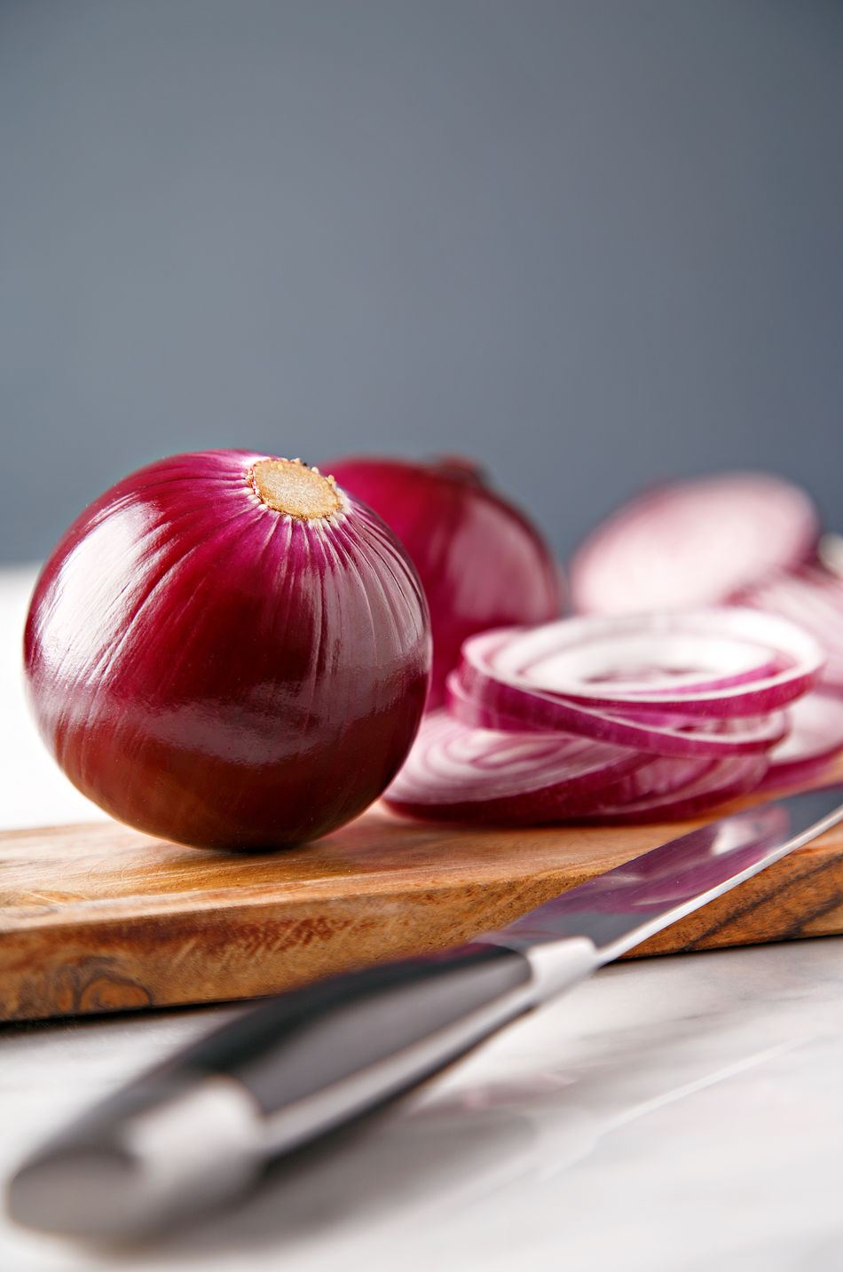 Red onions on a wooden chopping board with a knife on the side Chopping Chopping Board Close-up Food Freshness Healthy Eating Indoors  Knife No People Onion Ready-to-eat Red Onion Studio Shot Vegetable