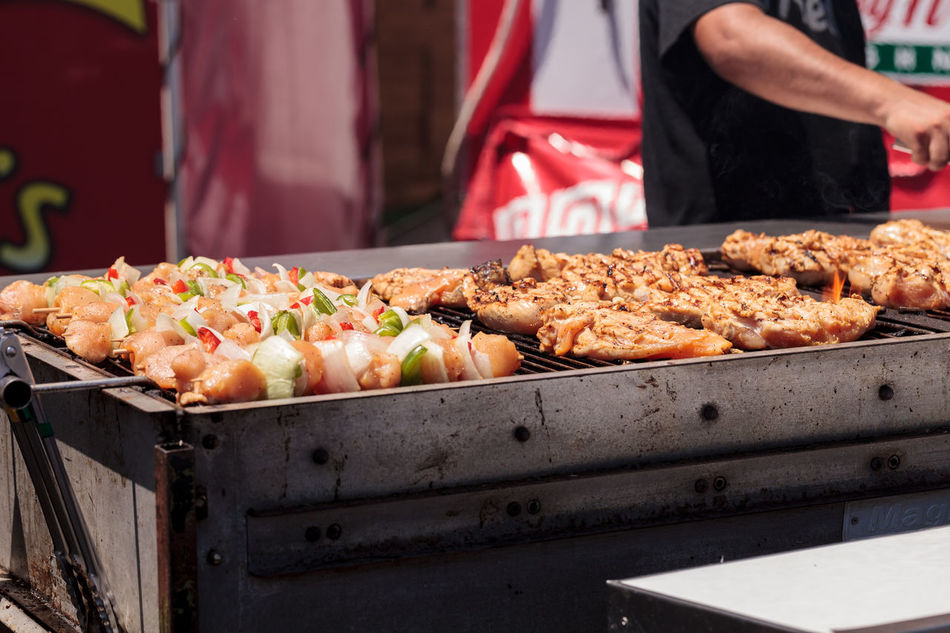 Chicken, beef and onion kabobs on a barbecue grill cooking at a fair ground. Adult Adults Only Barbecue BBQ Chicken Commercial Kitchen Day Food Food And Drink Freshness Grill Human Hand Kabob One Person Only Women Outdoors People Ready-to-eat Street Food