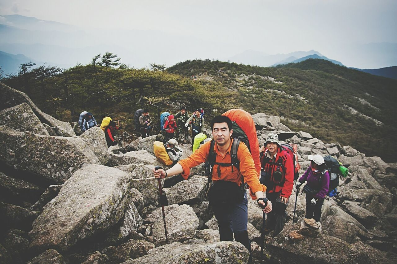 mountain, adventure, rock - object, mountain climbing, hiking, backpack, leisure activity, real people, mountain range, recreational pursuit, climbing, lifestyles, day, sky, rock climbing, togetherness, friendship, outdoors, nature, extreme sports, cliff, healthy lifestyle, sport, exercising, happiness, women, sports clothing, beauty in nature, standing, men, smiling, young adult, young women, adult, people