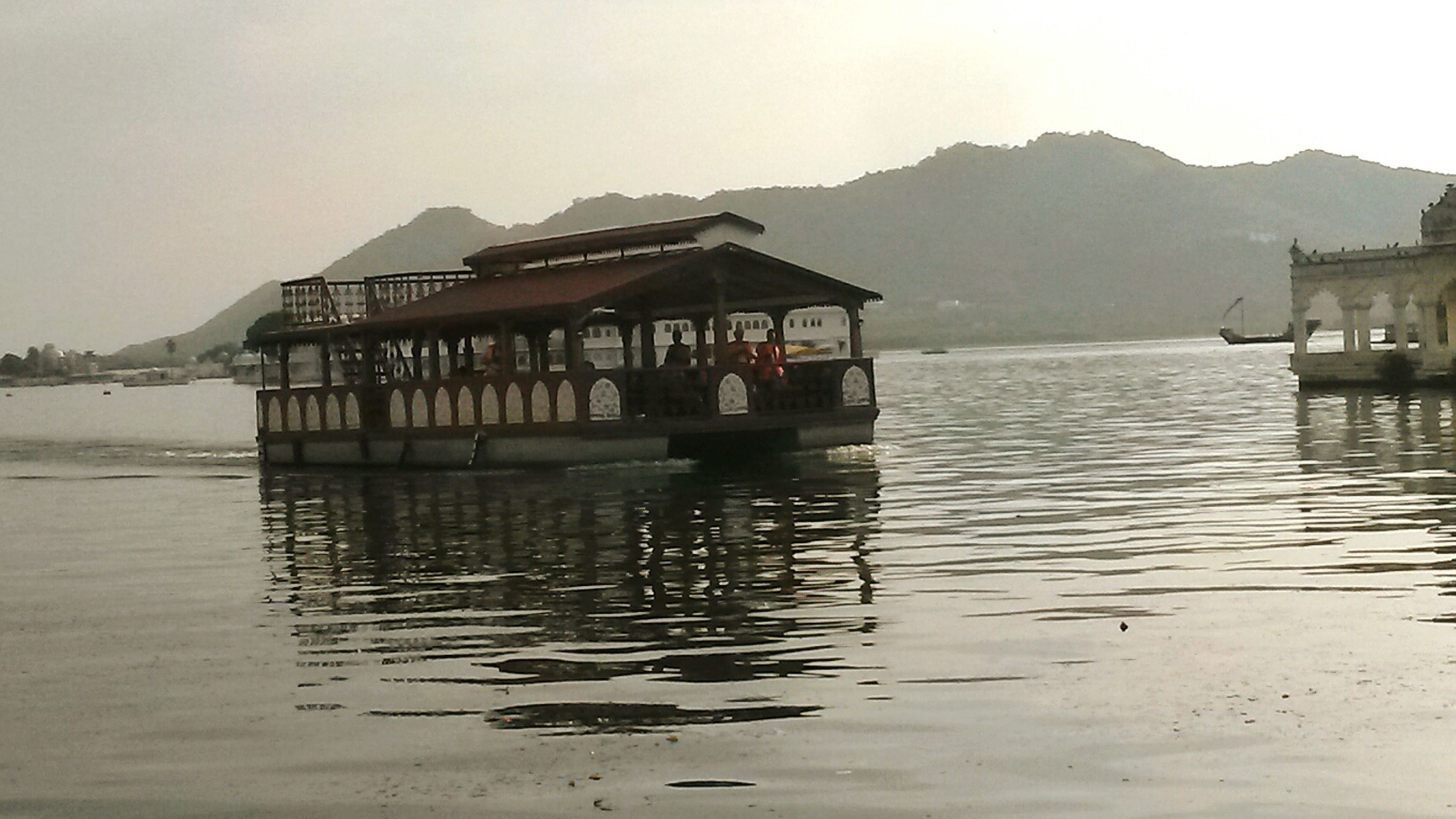 water, built structure, mountain, waterfront, architecture, building exterior, reflection, clear sky, nautical vessel, lake, transportation, tranquility, boat, house, scenics, tranquil scene, sky, mode of transport, pier, nature
