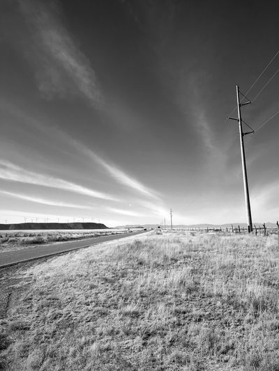 """""""Power Poles To Windmills"""" Across the vast rural area of Central New Mexico bringing dependable power to the scattered population is a challenge answered by a variety of sources from wind, solar and traditional power poles. Power Poles Power Lines New Mexico Photography New Mexico Black And White Photography Black And White Blackandwhite Field Sky Outdoors Nature No People Tranquil Scene Day Grass Scenics Landscape Industrial Windmill"""