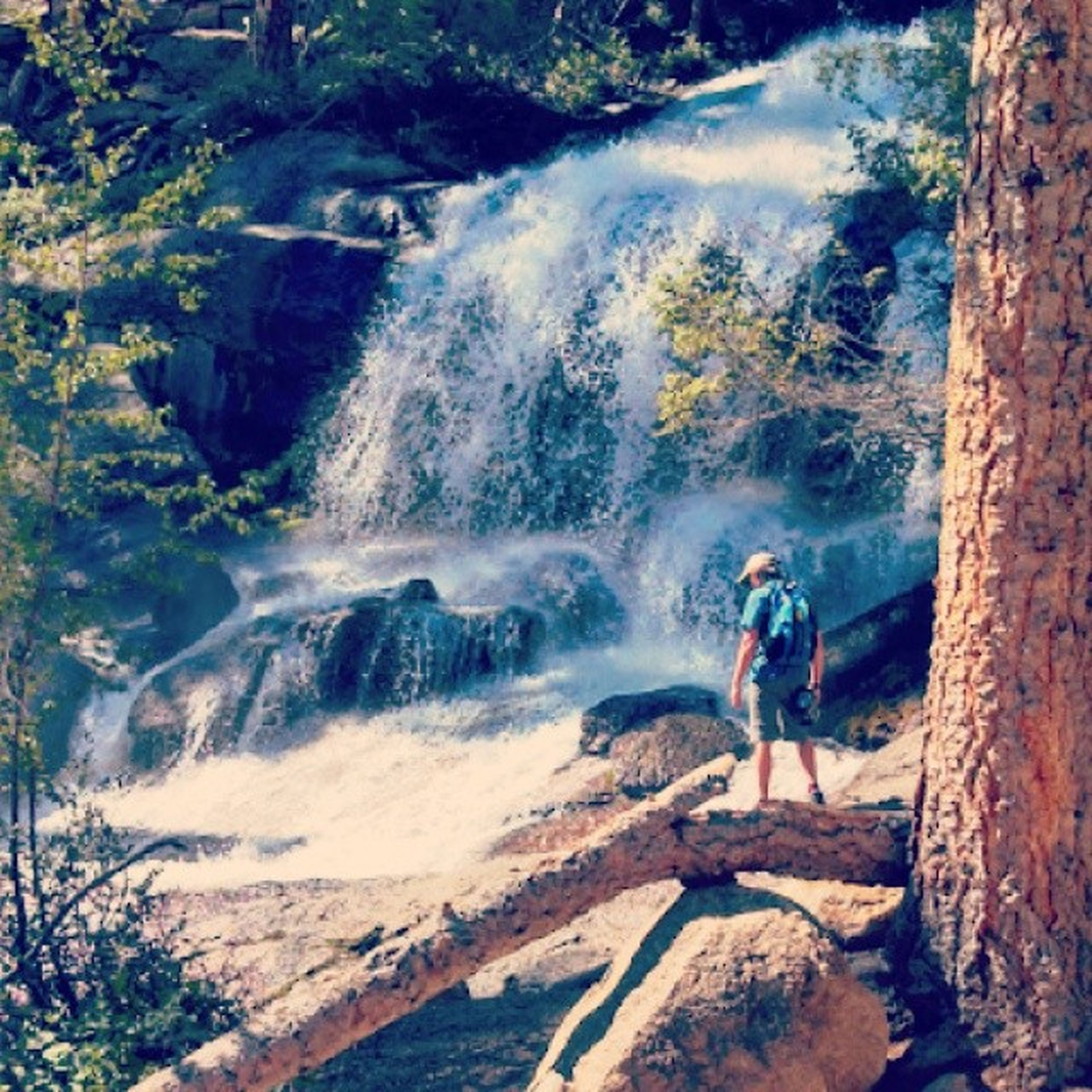lifestyles, leisure activity, full length, water, motion, waterfall, rock - object, men, adventure, vacations, casual clothing, nature, beauty in nature, rock formation, high angle view, travel, hiking, young men