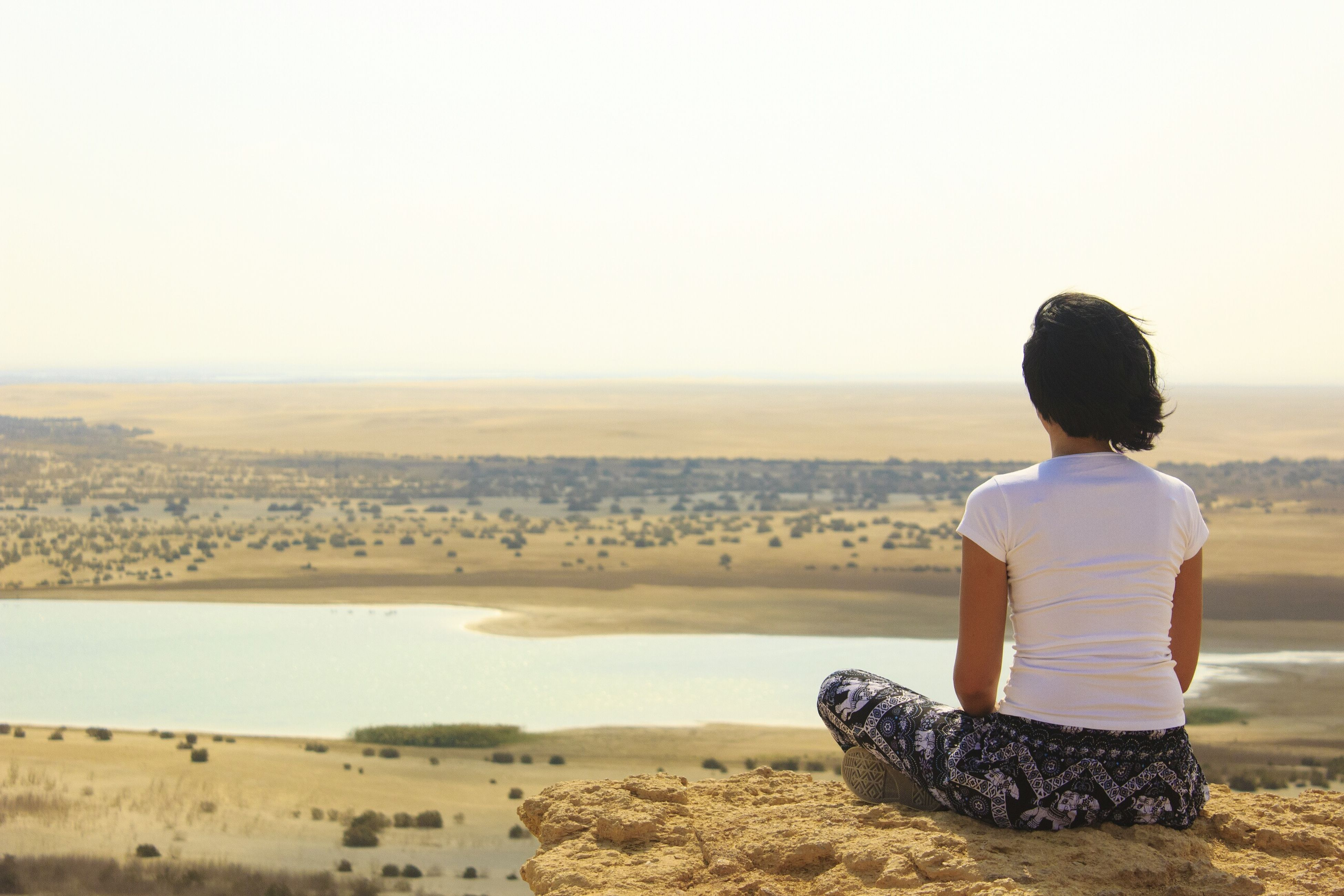rear view, beach, sea, sitting, water, one person, real people, nature, outdoors, clear sky, sand, beauty in nature, sky, leisure activity, scenics, horizon over water, day