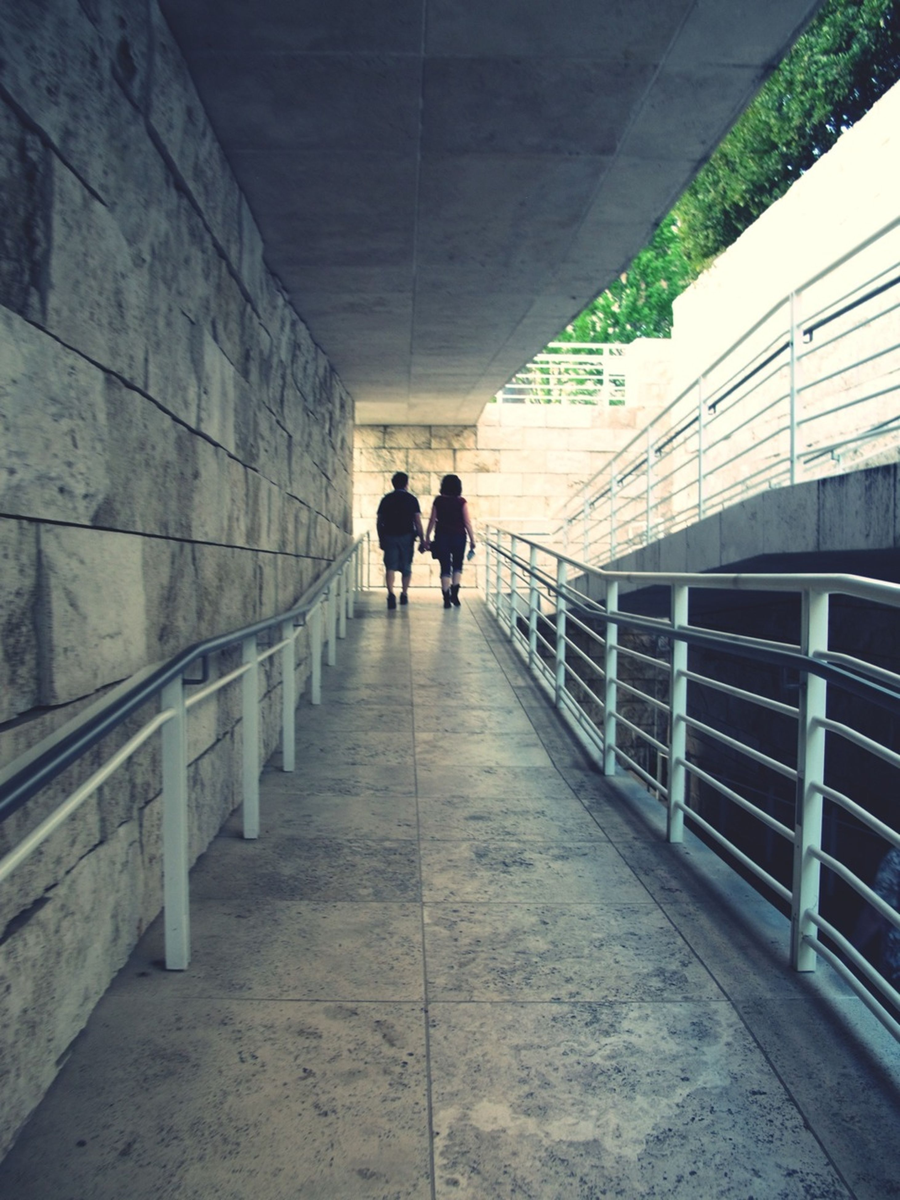 indoors, architecture, walking, full length, the way forward, rear view, men, built structure, lifestyles, tunnel, corridor, person, diminishing perspective, silhouette, wall - building feature, ceiling, leisure activity, arch