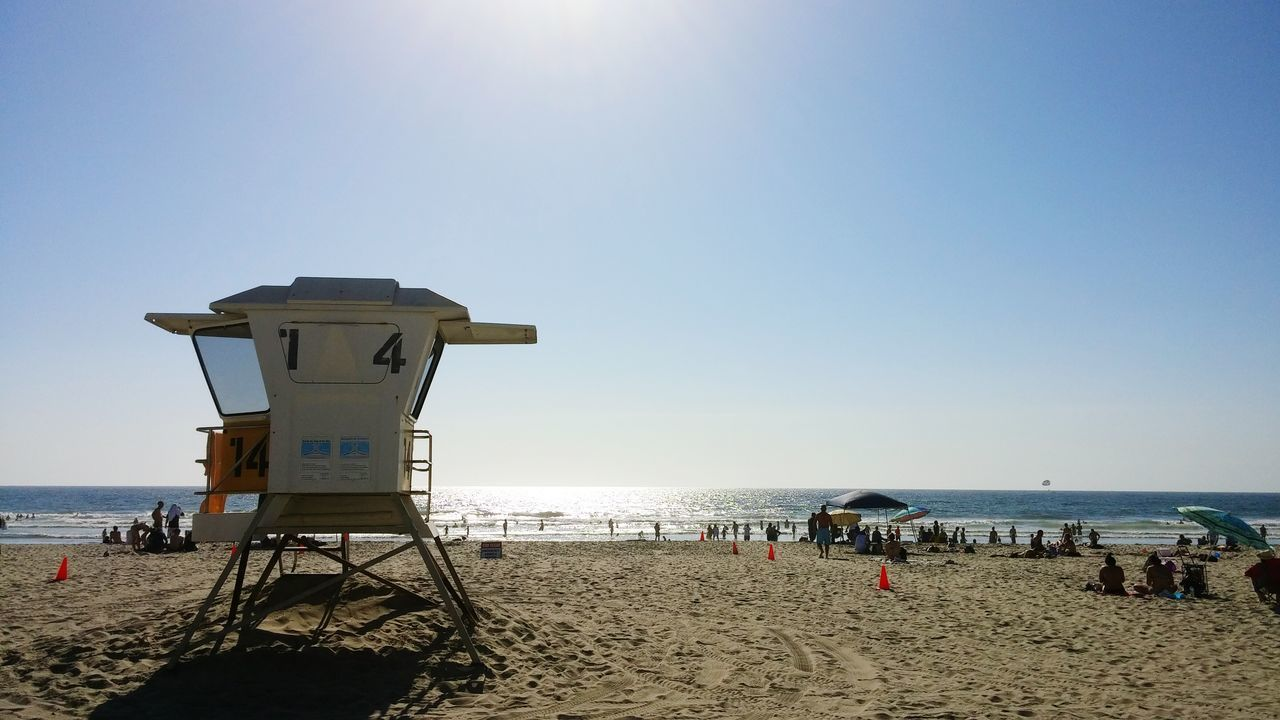 beach, sea, sand, horizon over water, water, lifeguard hut, clear sky, sunlight, shore, nature, lifeguard, protection, tranquil scene, scenics, beauty in nature, safety, outdoors, vacations, sky, tranquility, day, real people, blue, men, large group of people, people