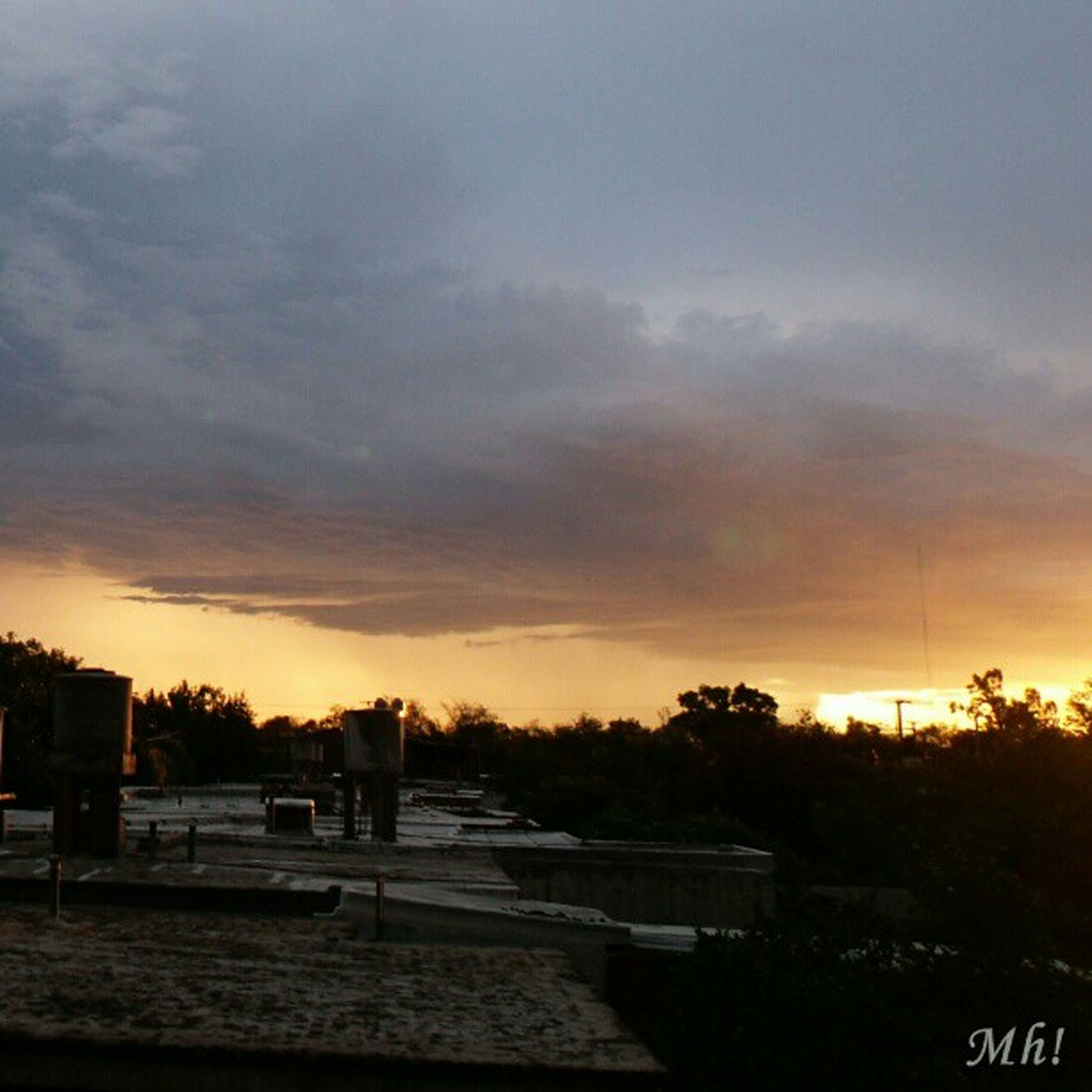 sunset, sky, cloud - sky, orange color, transportation, tree, land vehicle, mode of transport, silhouette, beauty in nature, car, scenics, nature, cloudy, built structure, road, water, building exterior, weather, tranquility