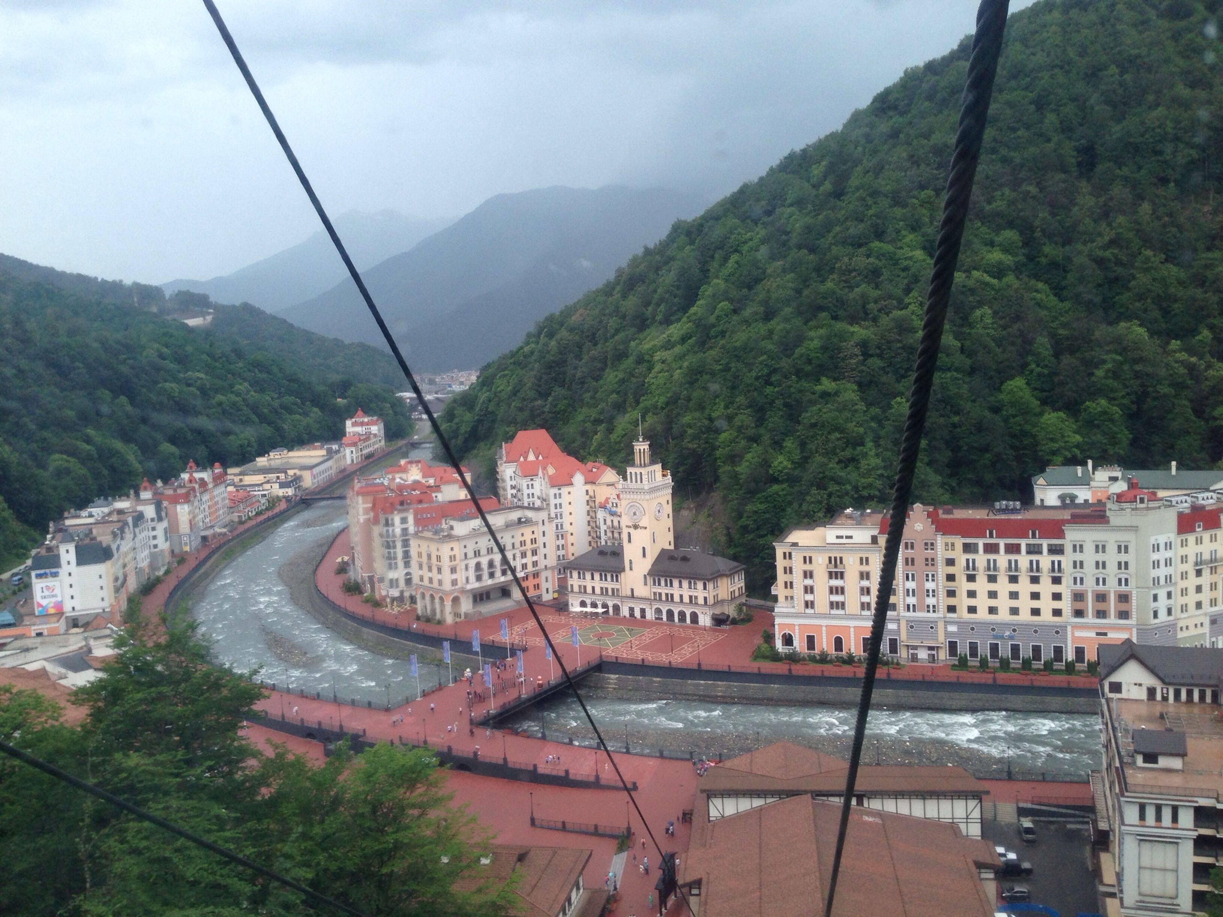 mountain, architecture, built structure, tree, building exterior, mountain range, transportation, high angle view, sky, connection, bridge - man made structure, road, river, house, day, outdoors, residential building, nature, residential structure, scenics