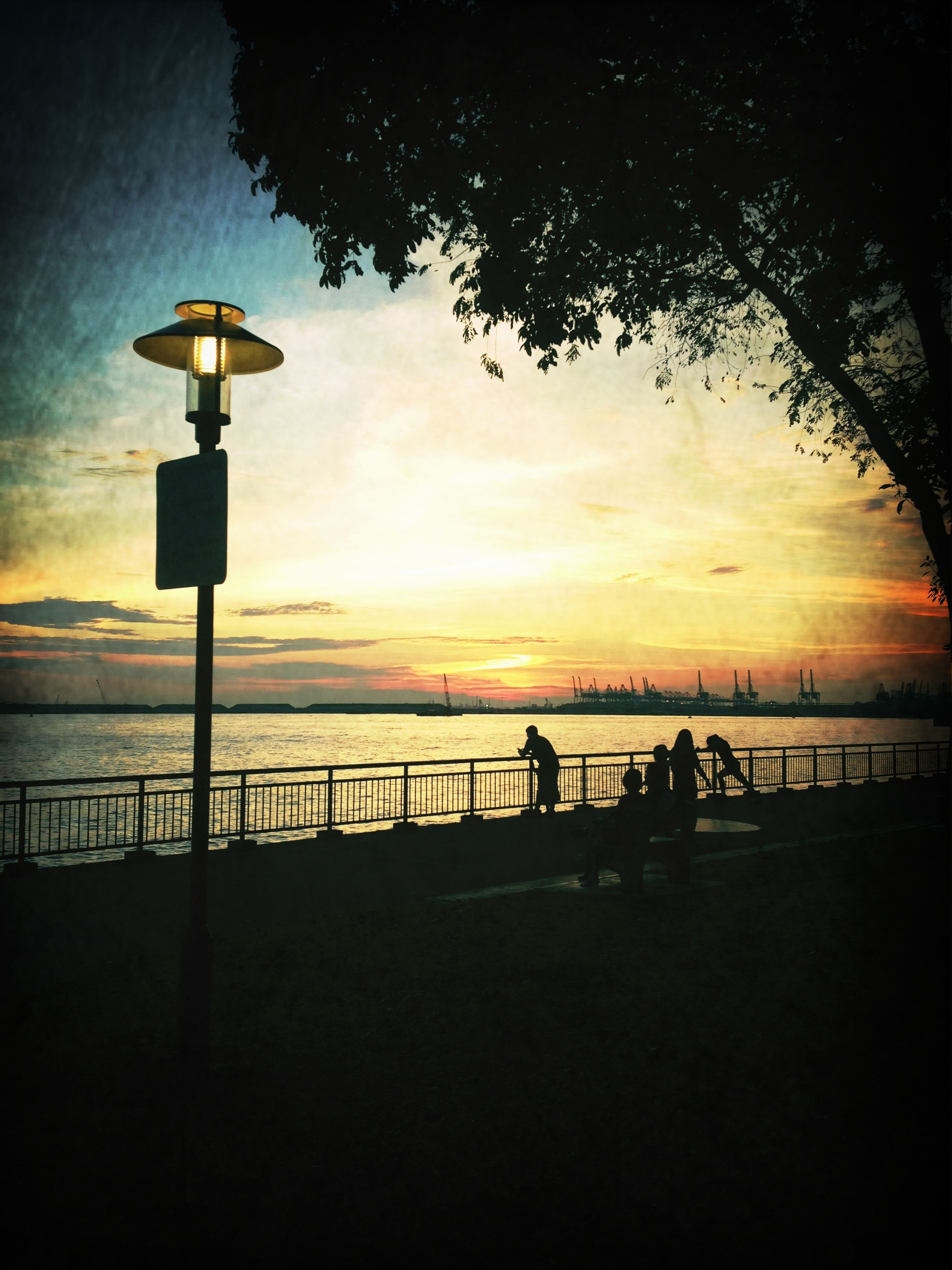 sunset, silhouette, sky, water, scenics, tranquility, sea, tranquil scene, beauty in nature, orange color, street light, railing, nature, idyllic, horizon over water, dusk, built structure, cloud - sky, lighting equipment, sun