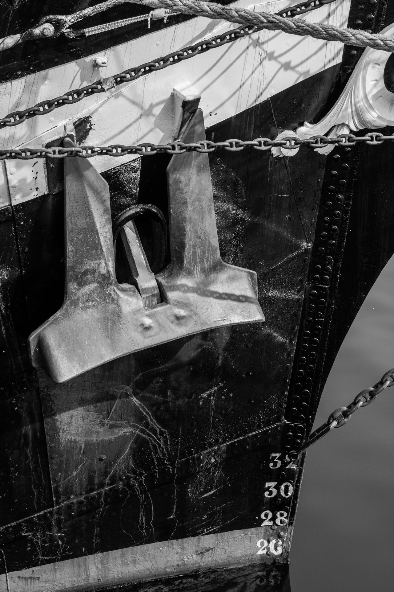 Anchor Black And White Calm Sea Chains Day Docks Iron Maritime Metal Monochrome Moored Nautical Nautical Vessel No People Outdoors Port Sea Ship Steel Stern Tall Ship Transportation Waterline