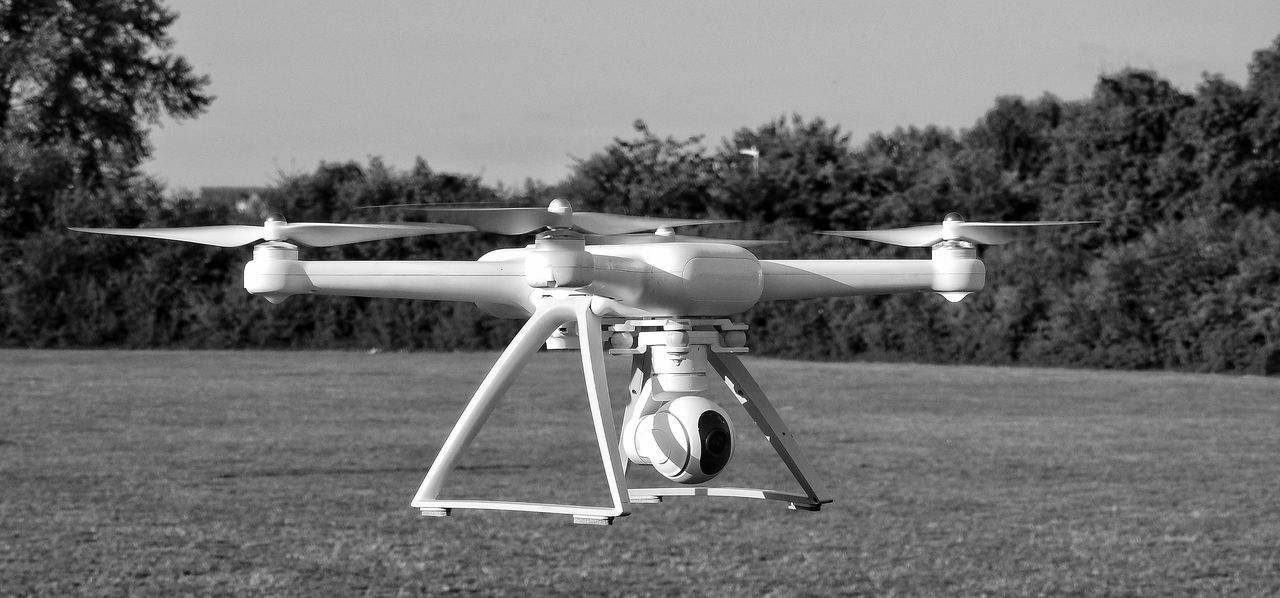 Mi Drone Xiaomi Hovering Monochrome Black And White Drone Shot Leisure Activity Summer Equipment Fly Time Flight Mi Playtime No People Technology Media Equipment Drone  New Toy A Kid With A New Toy Grass Outdoors Day Drone  Flying Sky