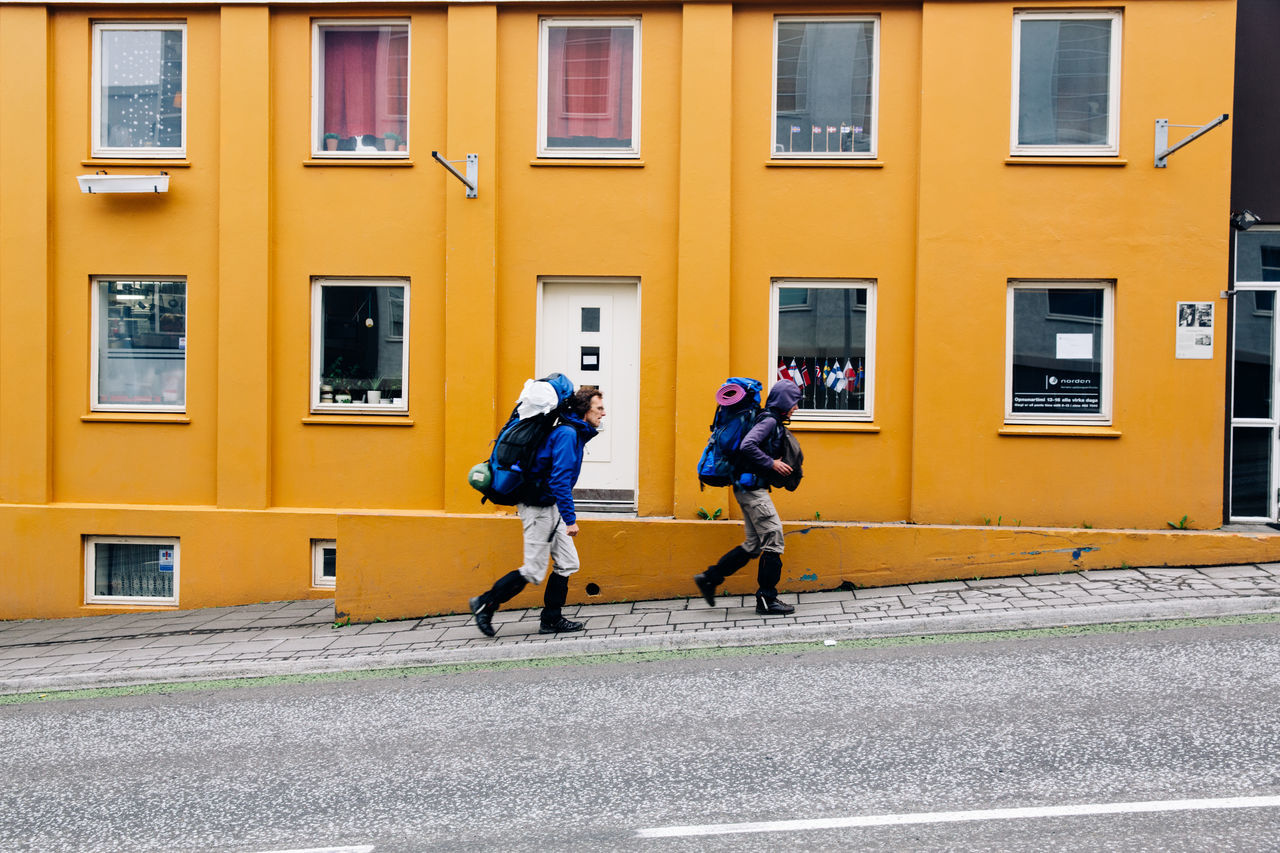 Two backpackers exploring Iceland Akureyri Backpacker Backpacking Boots Building Exterior Explorer Flags Hiking Hiking Trail Hill Road Iceland Memories Street Travel Traveller Trekking Uphill Windows Yellow Yellow Wall