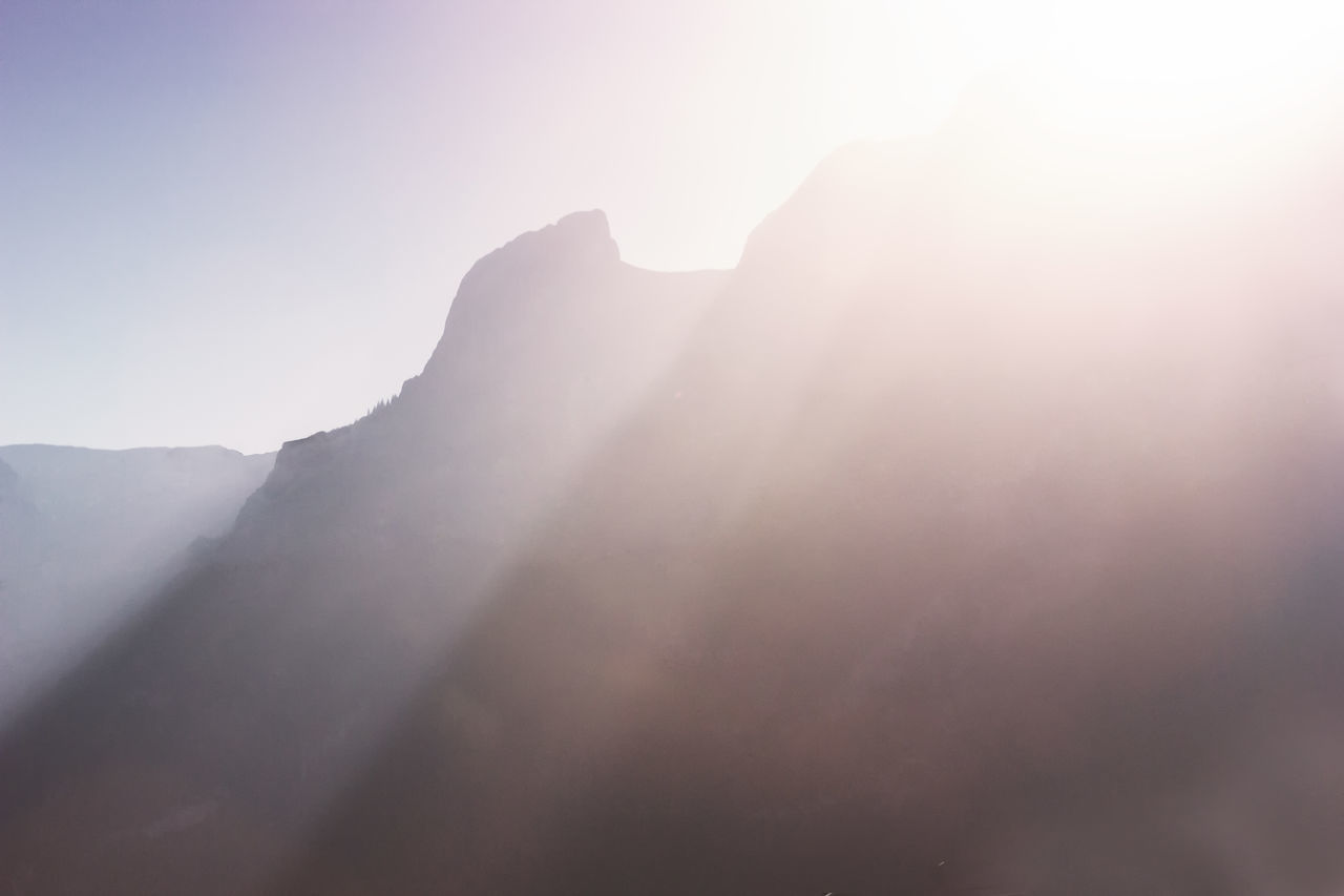 Panorama of the sun setting and sun beams over misty mountains Bright Dawn Fog Mist Mountain Mountain Range Nature No People Outdoors Panorama Powerful Rocks Scenics Sky Sun Beams Sunlight Sunset Tranquil Scene Tranquility
