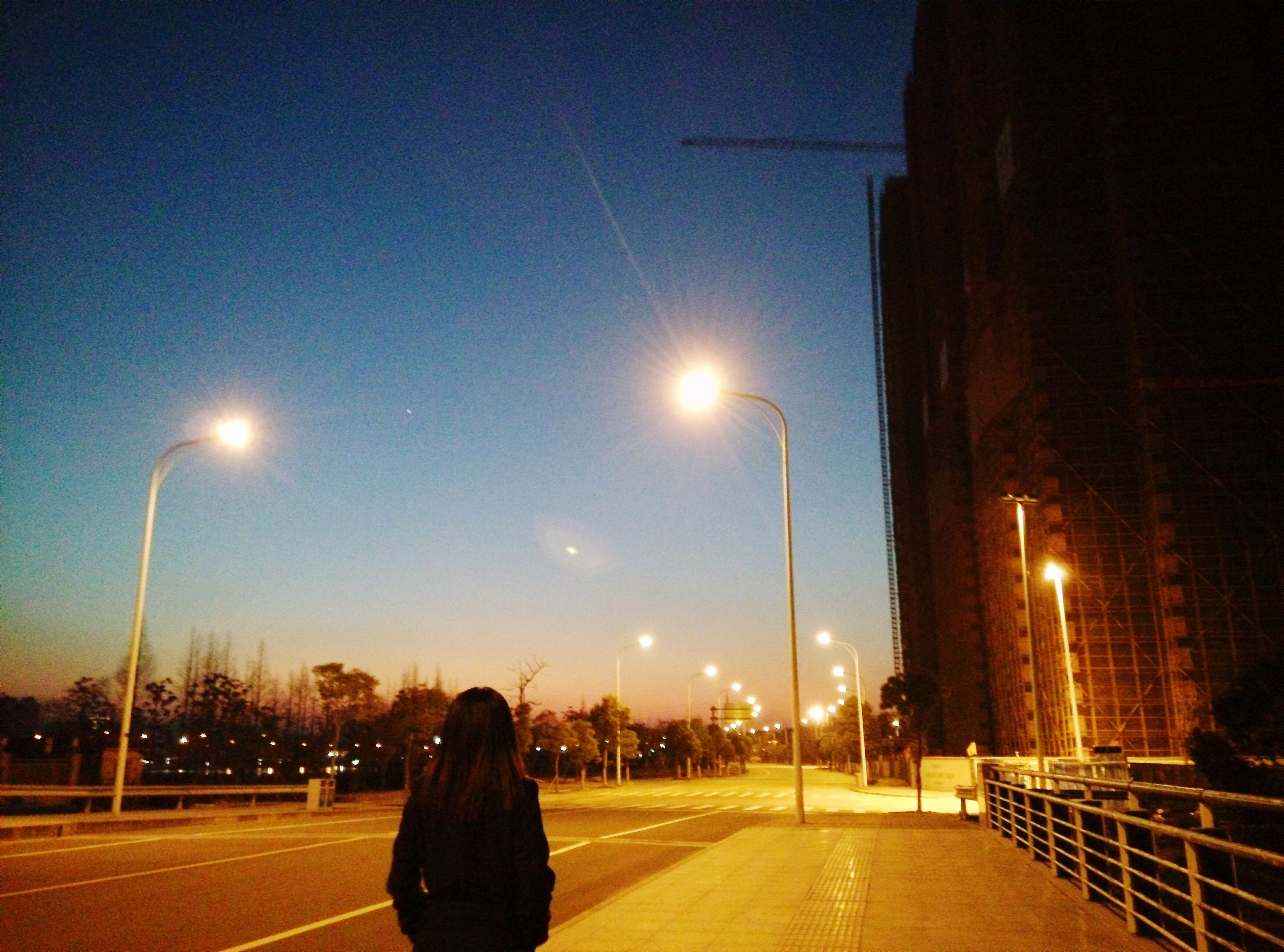 illuminated, street light, night, the way forward, road, street, lighting equipment, transportation, sky, diminishing perspective, city, clear sky, vanishing point, road marking, building exterior, car, blue, lens flare, dusk, one person