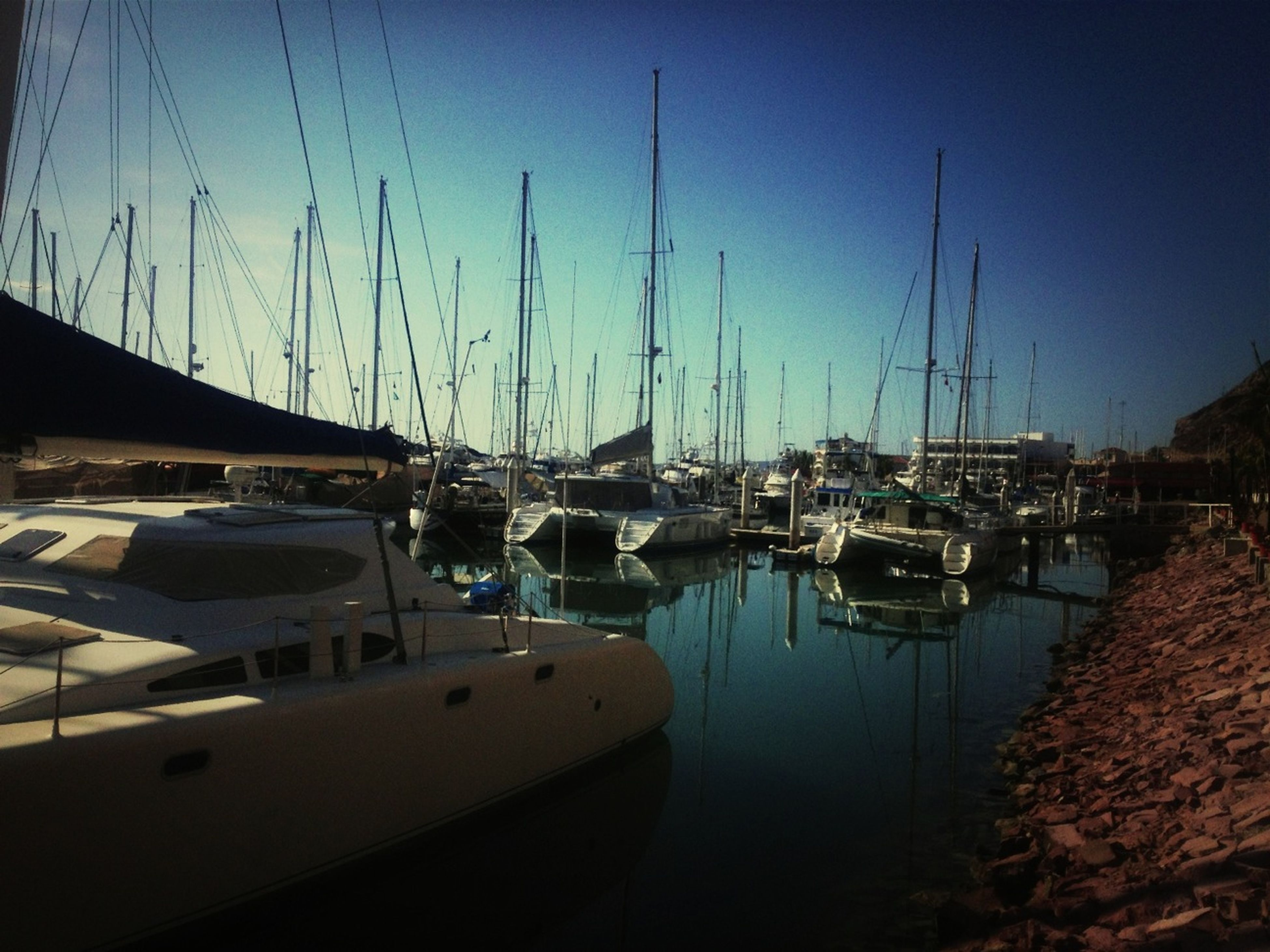 nautical vessel, moored, boat, transportation, water, mode of transport, mast, harbor, sailboat, sea, reflection, sky, waterfront, marina, blue, clear sky, yacht, nature, in a row, group of objects