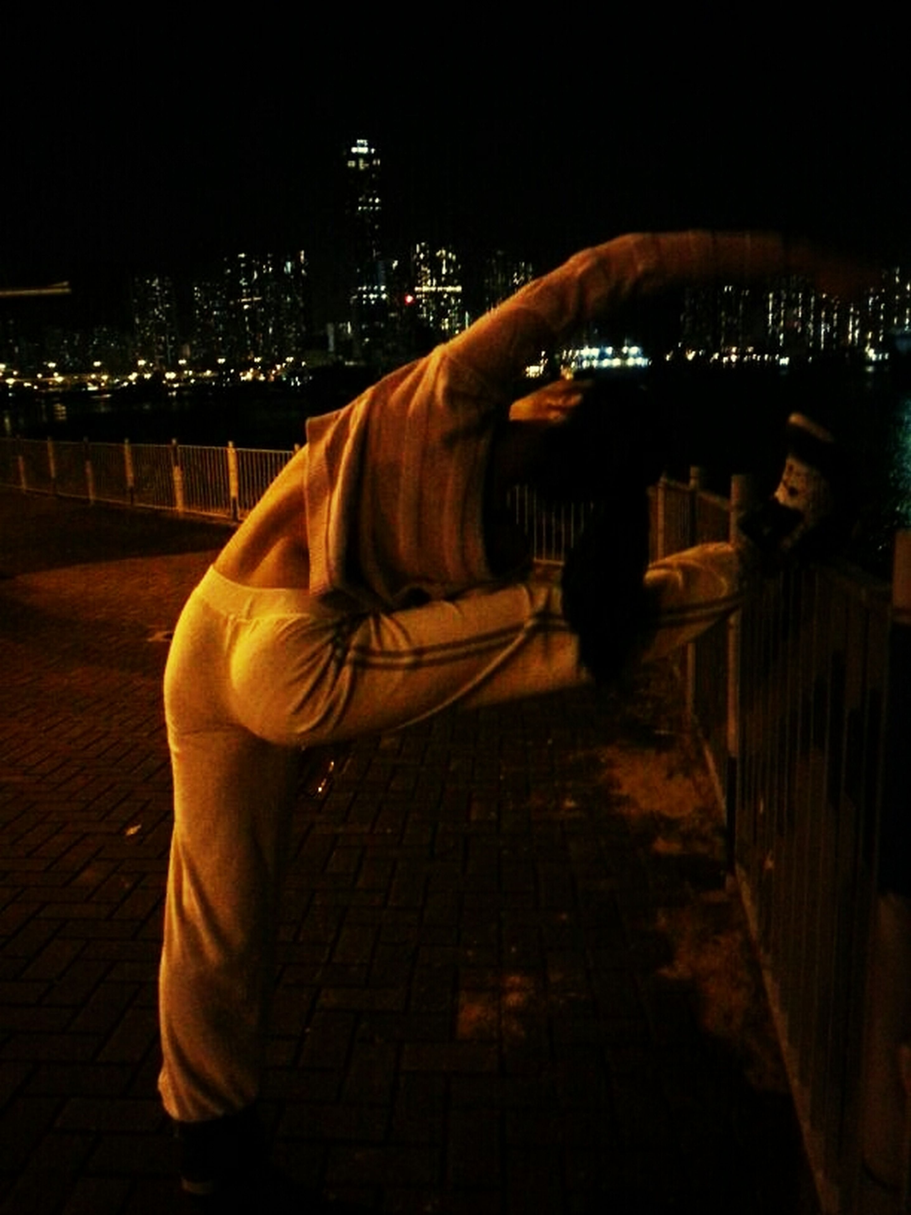night, illuminated, architecture, city, built structure, building exterior, lifestyles, men, cityscape, rear view, city life, leisure activity, dark, person, lighting equipment, standing, full length, outdoors