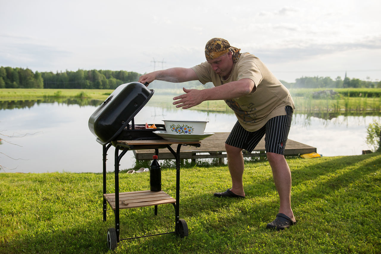 a man grill meat Barbecue Broil Celebration Day Field Food And Drink Full Length Grass Grill Grilled Grilled Meat Holiday Humor Lake Lakeshore Leisure Activity Lifestyles Nature One Person Outdoors Real People Sky Standing Vacations Water Sommergefühle