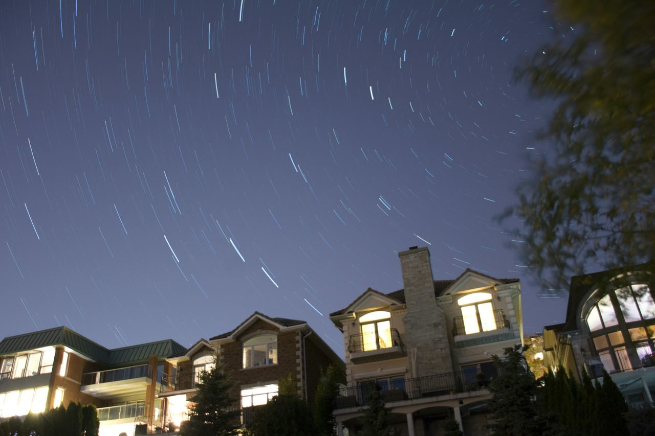 night, building exterior, illuminated, architecture, star - space, long exposure, built structure, star trail, low angle view, astronomy, outdoors, no people, sky, star field, residential building, motion, street light, nature, constellation, starry, galaxy