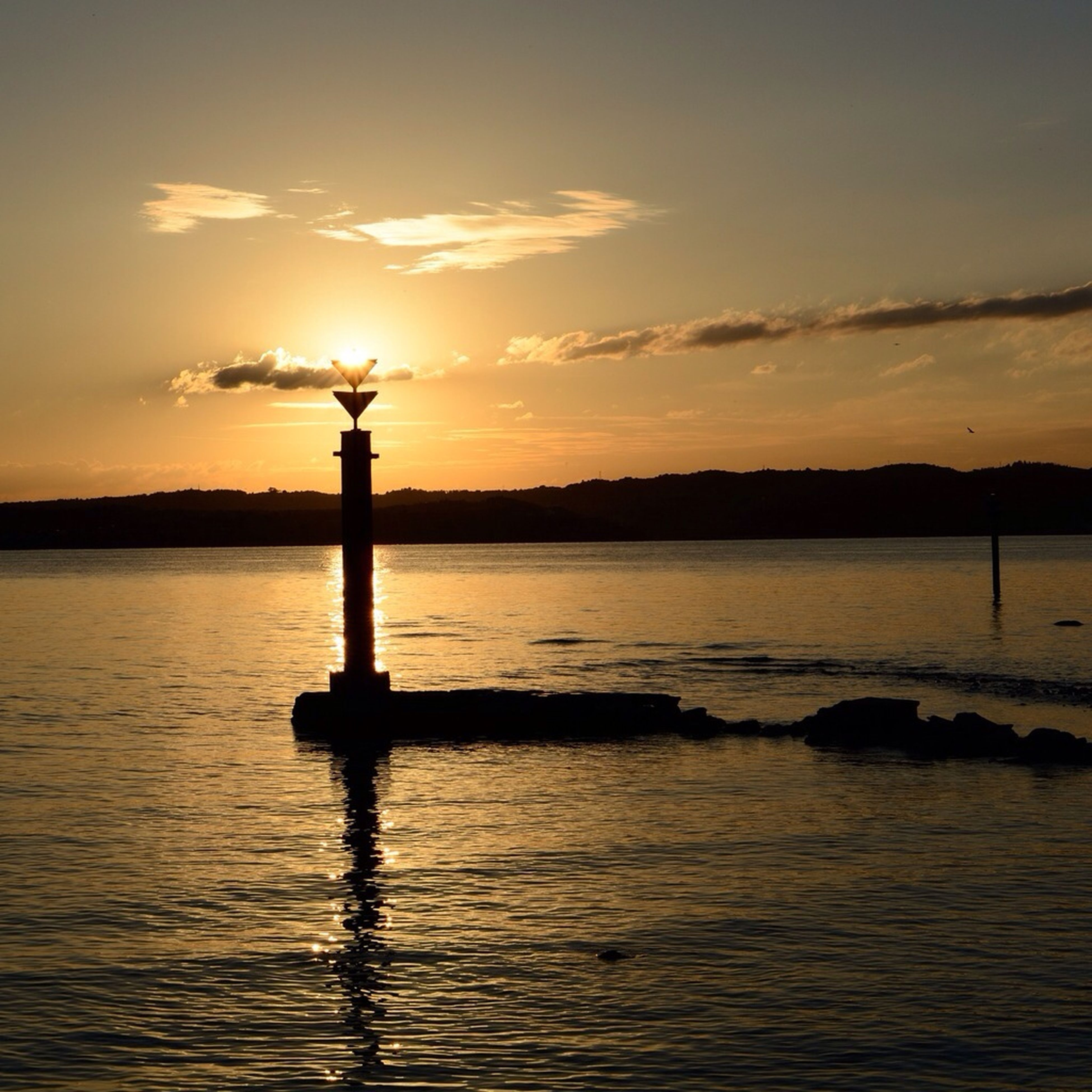 sunset, water, silhouette, sky, waterfront, tranquility, scenics, tranquil scene, beauty in nature, sea, orange color, sun, rippled, reflection, nature, idyllic, lake, wooden post, cloud - sky, cloud
