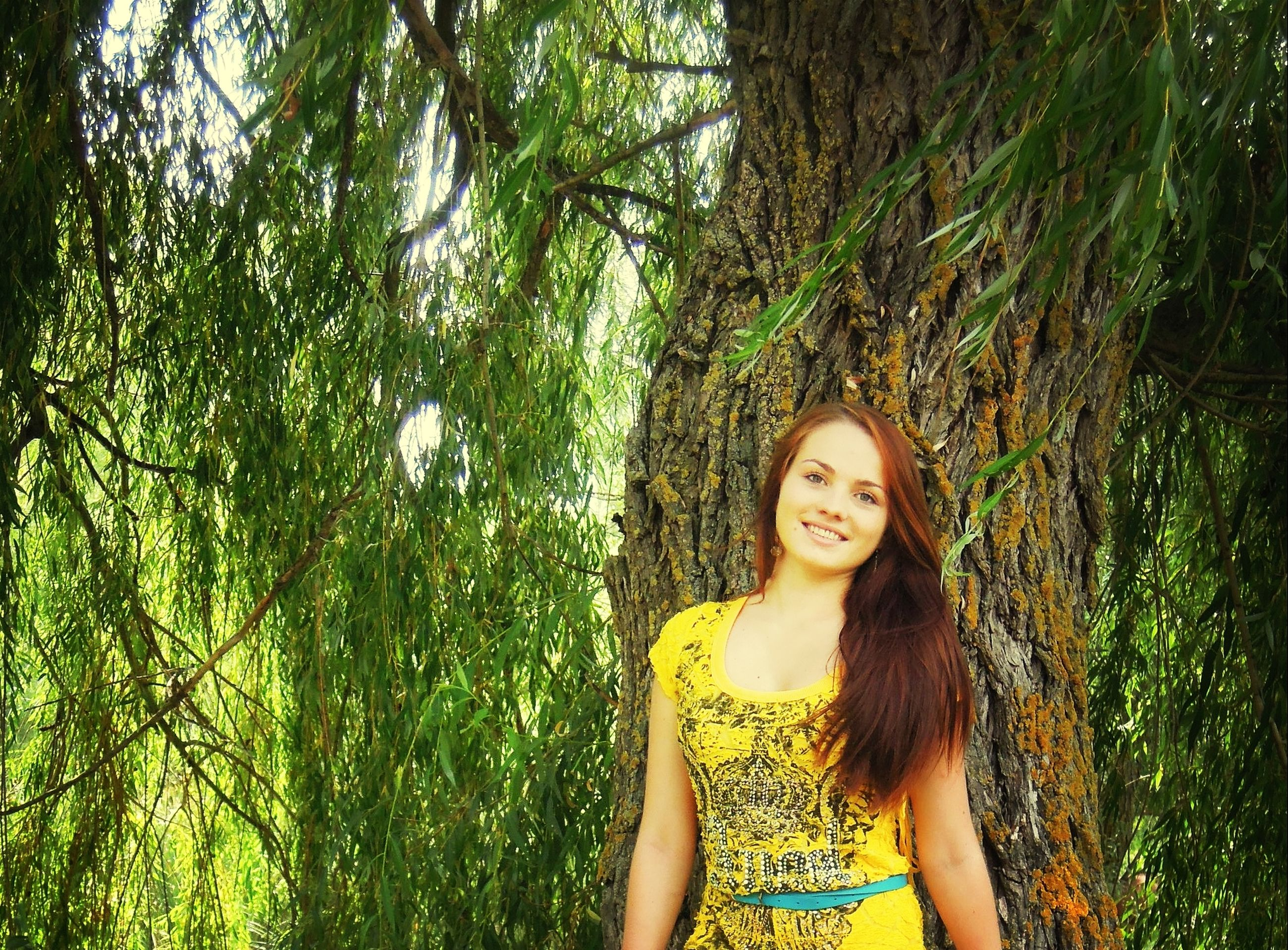 young adult, young women, tree, lifestyles, person, leisure activity, looking at camera, portrait, long hair, casual clothing, front view, smiling, standing, growth, green color, tree trunk, nature