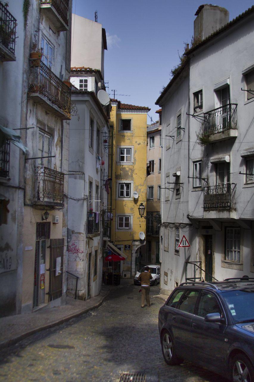 Rear view of man walking on narrow lane along buildings