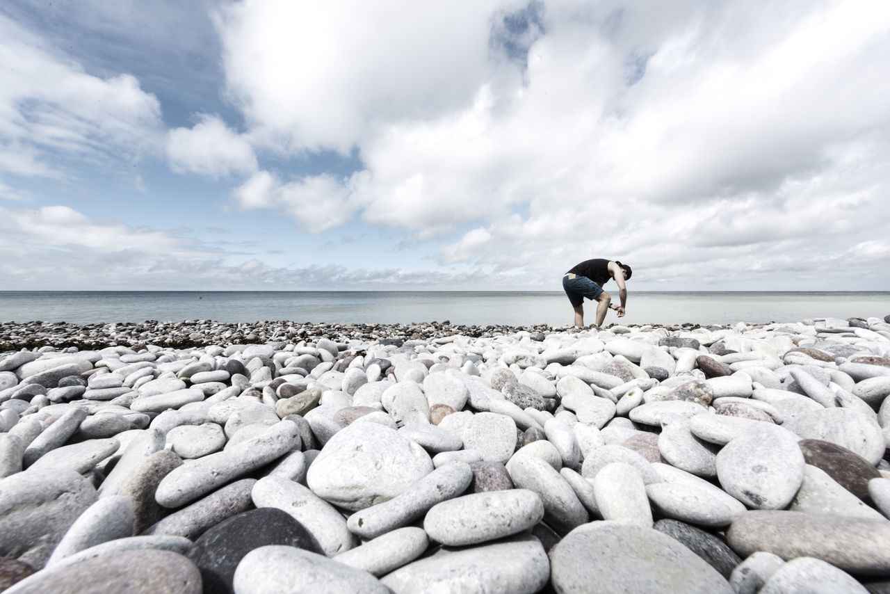 Collecting stones. Beauty In Nature Cloud Cloud - Sky Cloudy Day Horizon Over Water Idyllic Lifestyles Nature Niklasskur Outdoors Pebble Pets Popular Photos Rock - Object Scenics Sea Shore Showcase April Sky Stone - Object The KIOMI Collection Tranquil Scene Tranquility Water