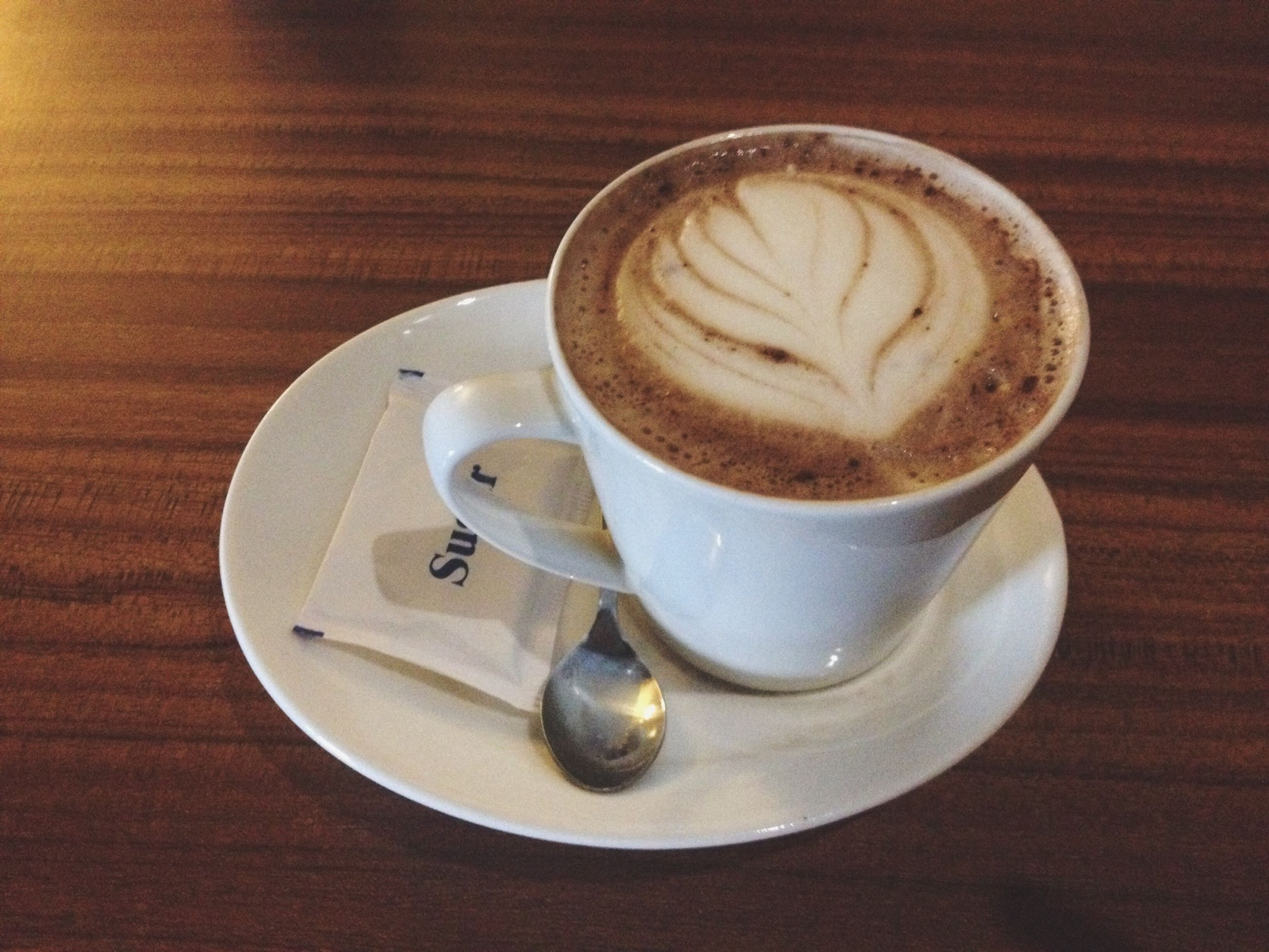 coffee cup, drink, food and drink, refreshment, saucer, coffee - drink, table, indoors, coffee, frothy drink, cappuccino, freshness, froth art, cup, still life, spoon, close-up, high angle view, beverage, latte