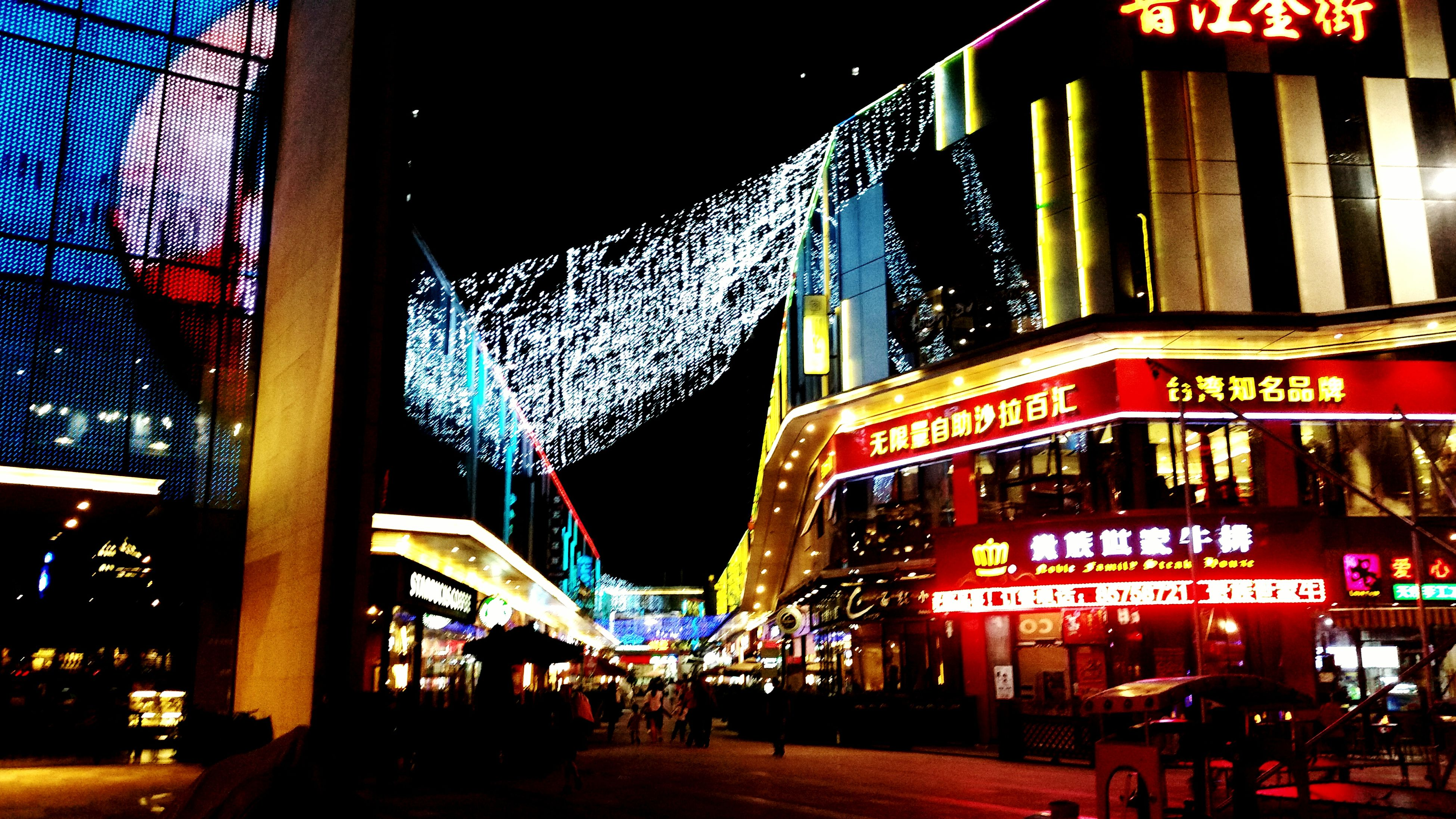 illuminated, night, city, building exterior, architecture, built structure, incidental people, low angle view, city life, lighting equipment, modern, travel destinations, neon, decoration, nightlife, tourism, electric light, outdoors, skyscraper, sky, multi colored, commercial sign, fairy lights