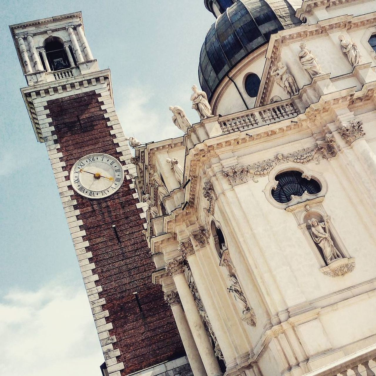 low angle view, building exterior, architecture, religion, built structure, place of worship, spirituality, day, outdoors, no people, sky, clock tower, bell tower, clock, travel destinations, history, bell, cloud - sky, time
