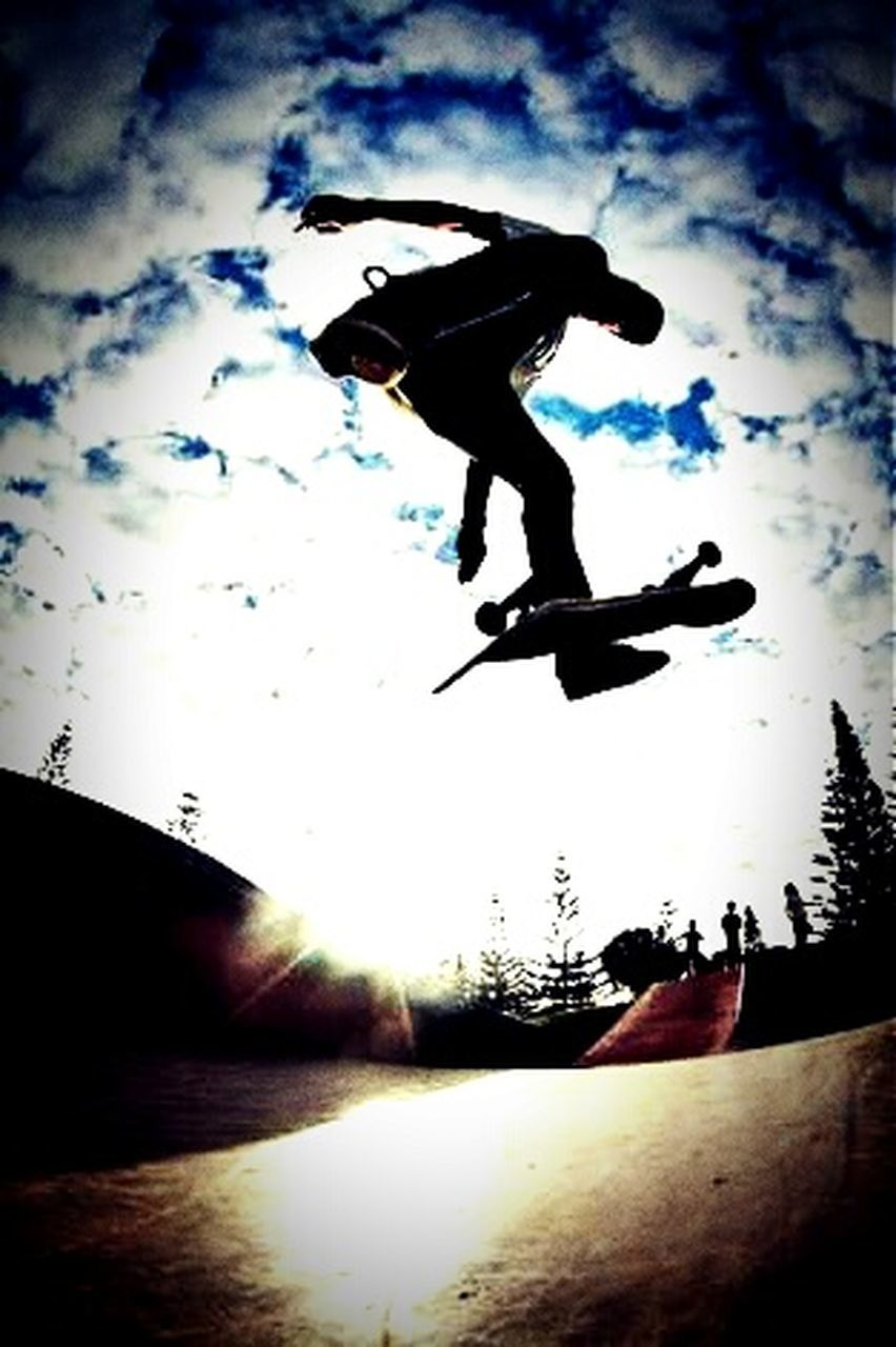 full length, silhouette, sky, mid-air, one person, cloud - sky, balance, outdoors, motion, skill, men, jumping, sport, sunlight, day, low angle view, extreme sports, real people, one man only, one young man only, nature, only men, stunt, snowboarding, adult, young adult, people, energetic, sportsman, skateboard park, adults only