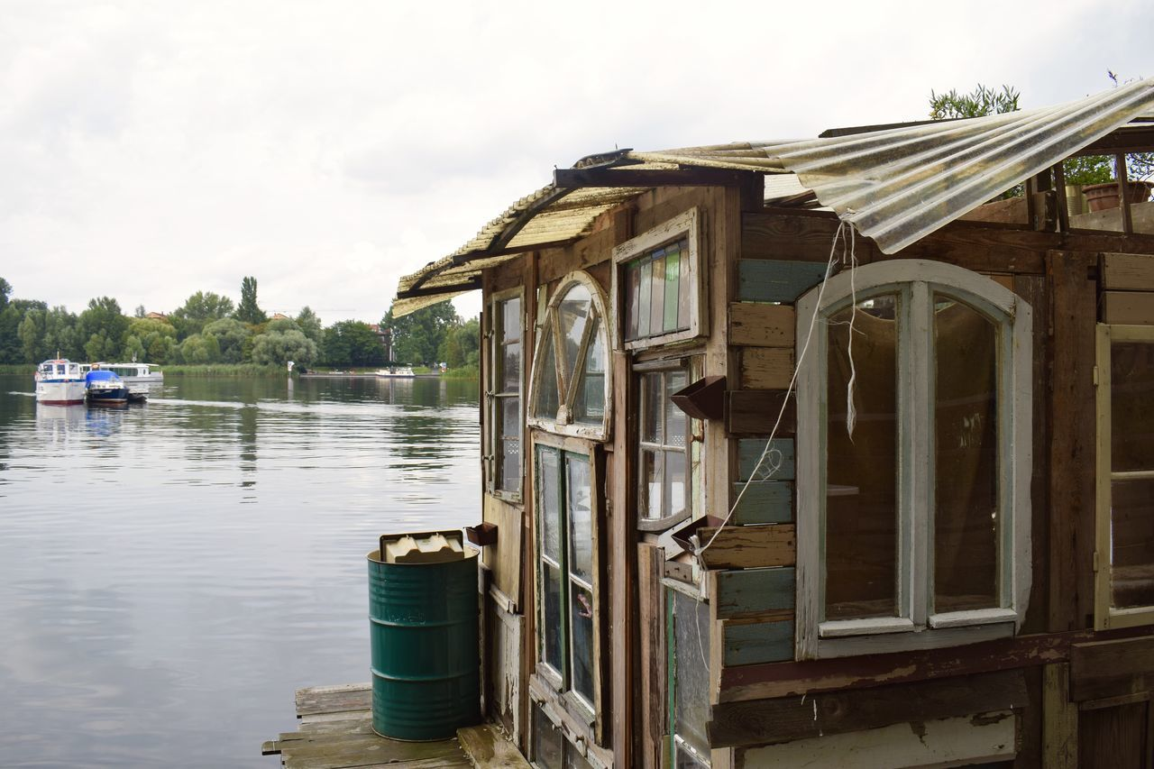 Wandr Berlin selection: Rummelsburger houseboat. photo: Rémy Baurichter Barrel Berlin Grey Sky Houseboat Raft Ramshackle Rummelsburger Bucht Spree Water Wooden